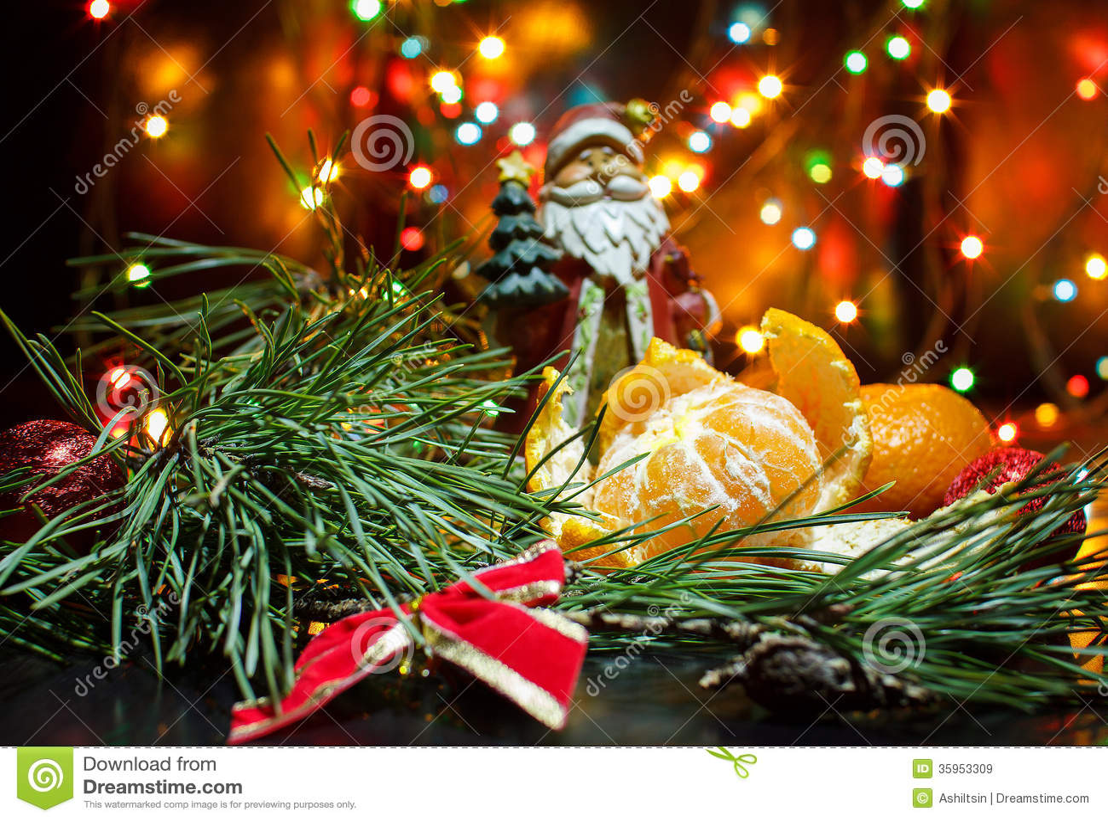 Mandarines en las ramas de un pino y de una guirnalda de la Navidad