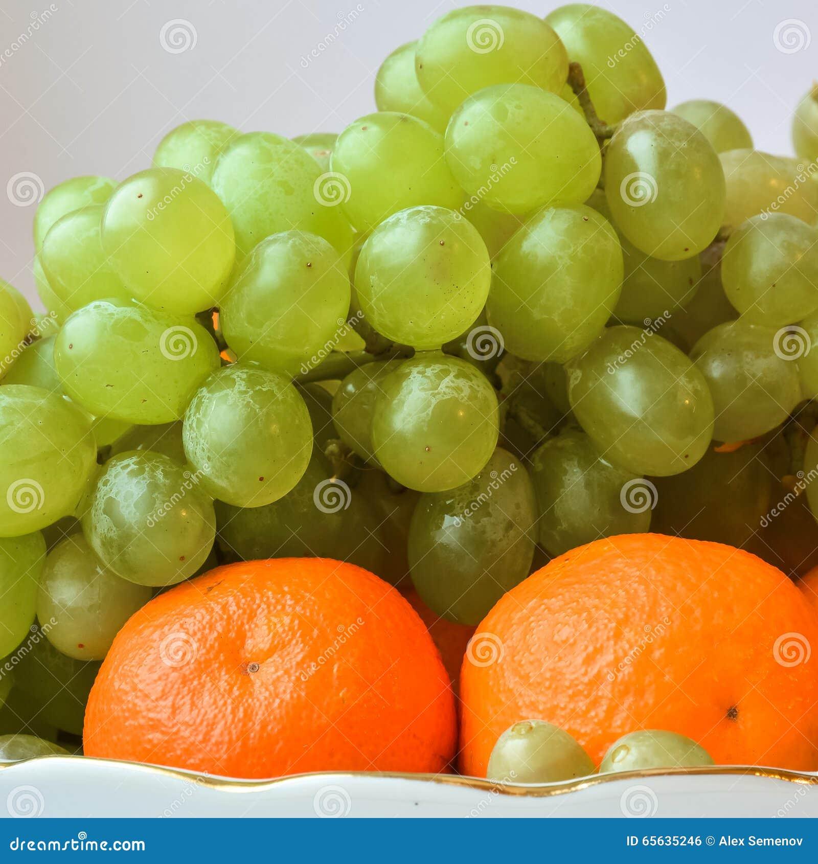 Mandarines lumineuses et juteuses, sur le dessus par groupe de raisins