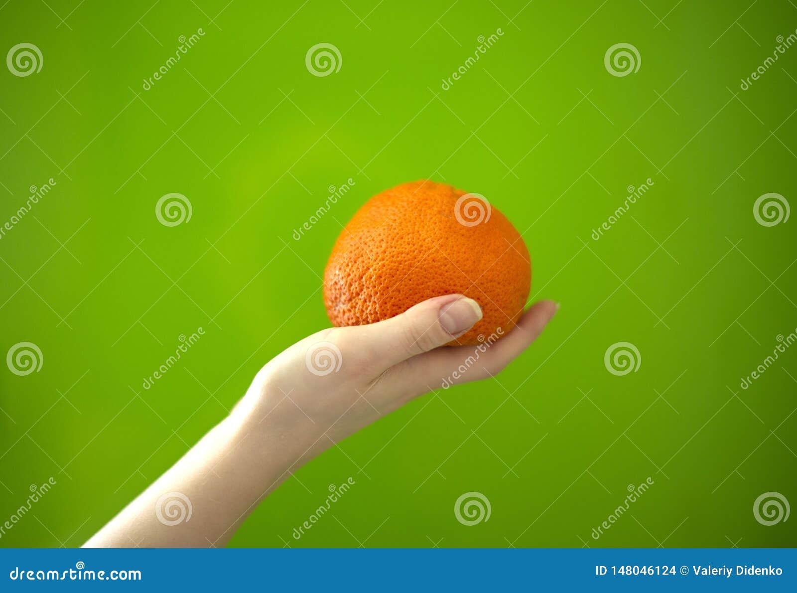Mandaryn w ręce na zielonym tle