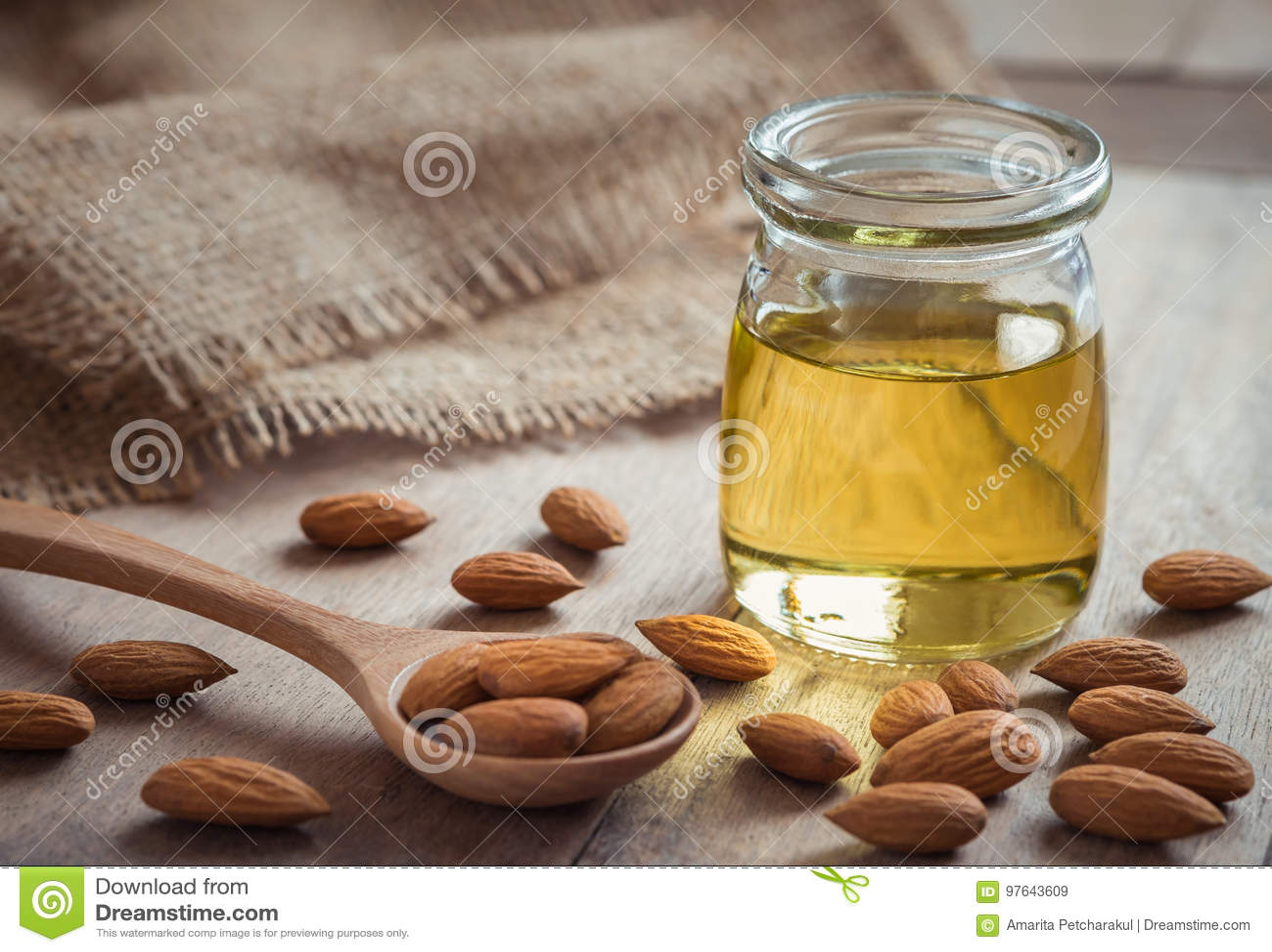 Mandelolja i glasflaska och mandlar på trätabellen