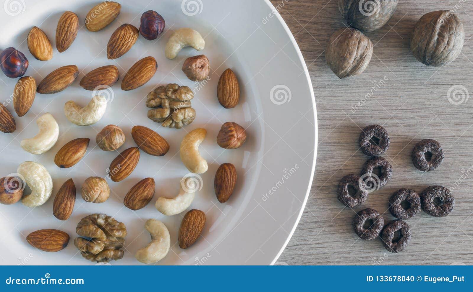 Mandorle, nocciole, noci, anacardi su un piatto bianco, tre intere noci, interi cereali croccanti del grano intorno all avena su