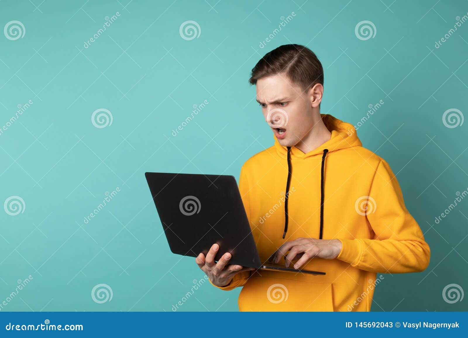 Maneger virado irritado no portátil amarelo e em gritar da terra arrendada do hoodie