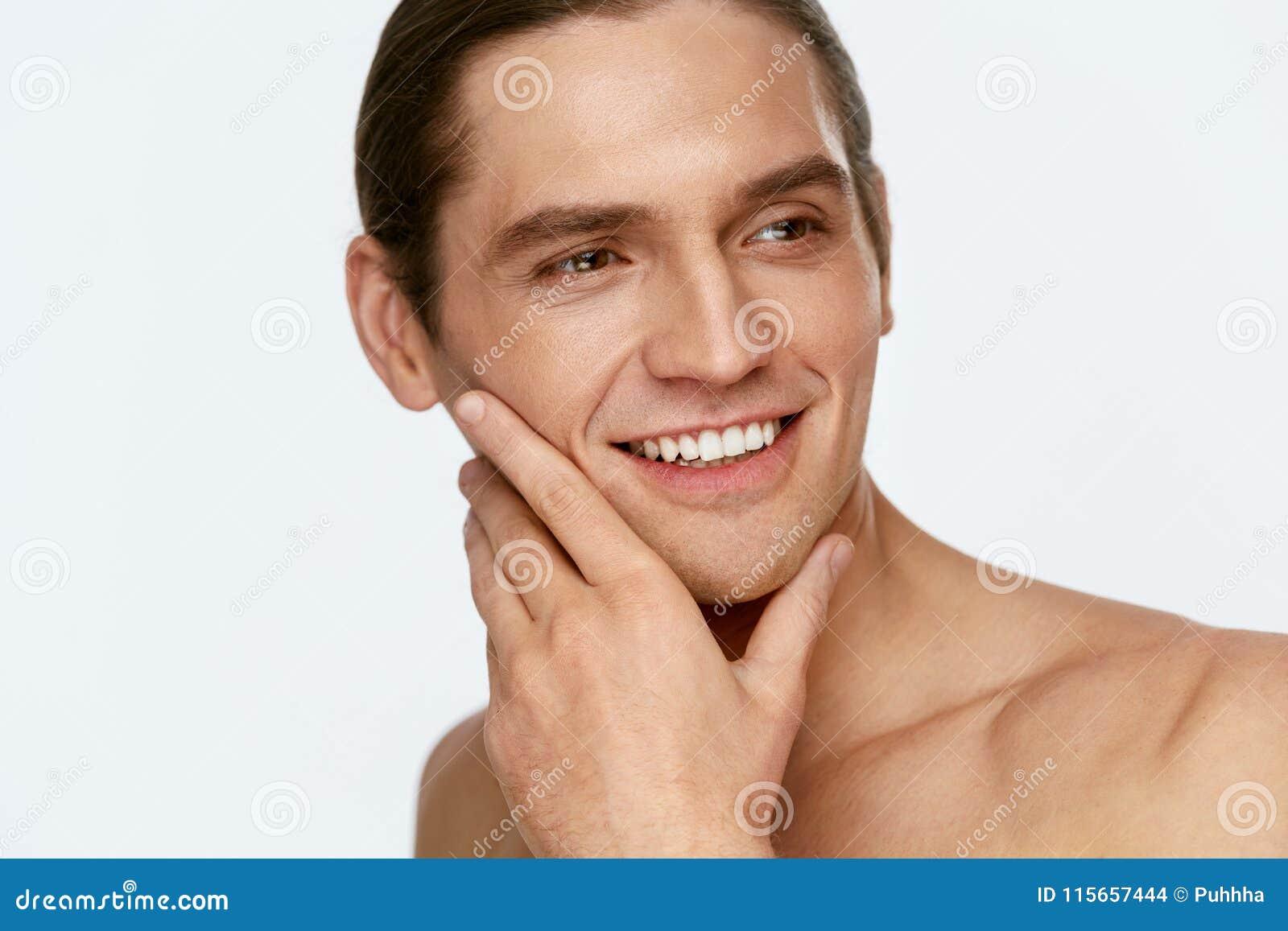 Manframsidaomsorg Den rörande mannen slätar hud, når han har rakat