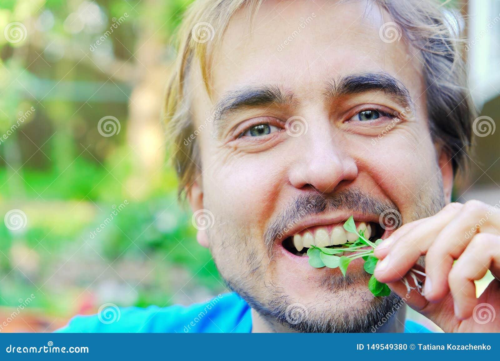 Mangeur d hommes adulte heureux a fra?chement s?lectionn? des verts micro des pousses de salade de fus?e ext?rieures Concept orga