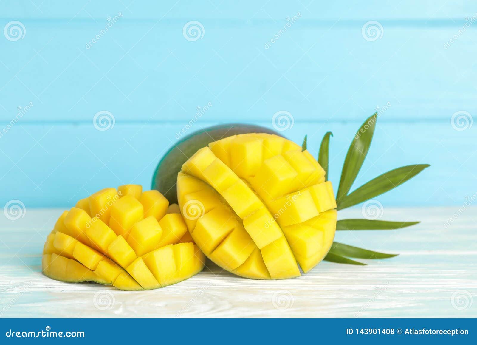 Manghi e foglia di palma maturi tagliati sulla tavola bianca contro il fondo di colore