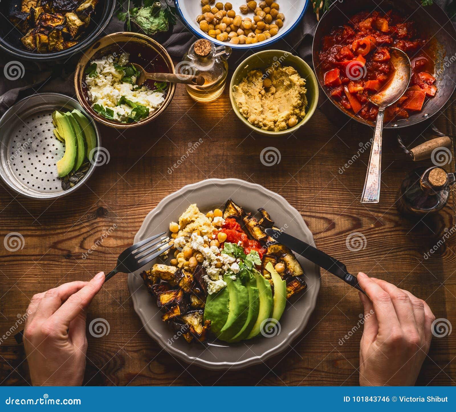 Mangiando il pasto vegetariano sano in ciotola con i ceci passi, verdure arrostite, pomodori rossi della paprica stufano, avocado