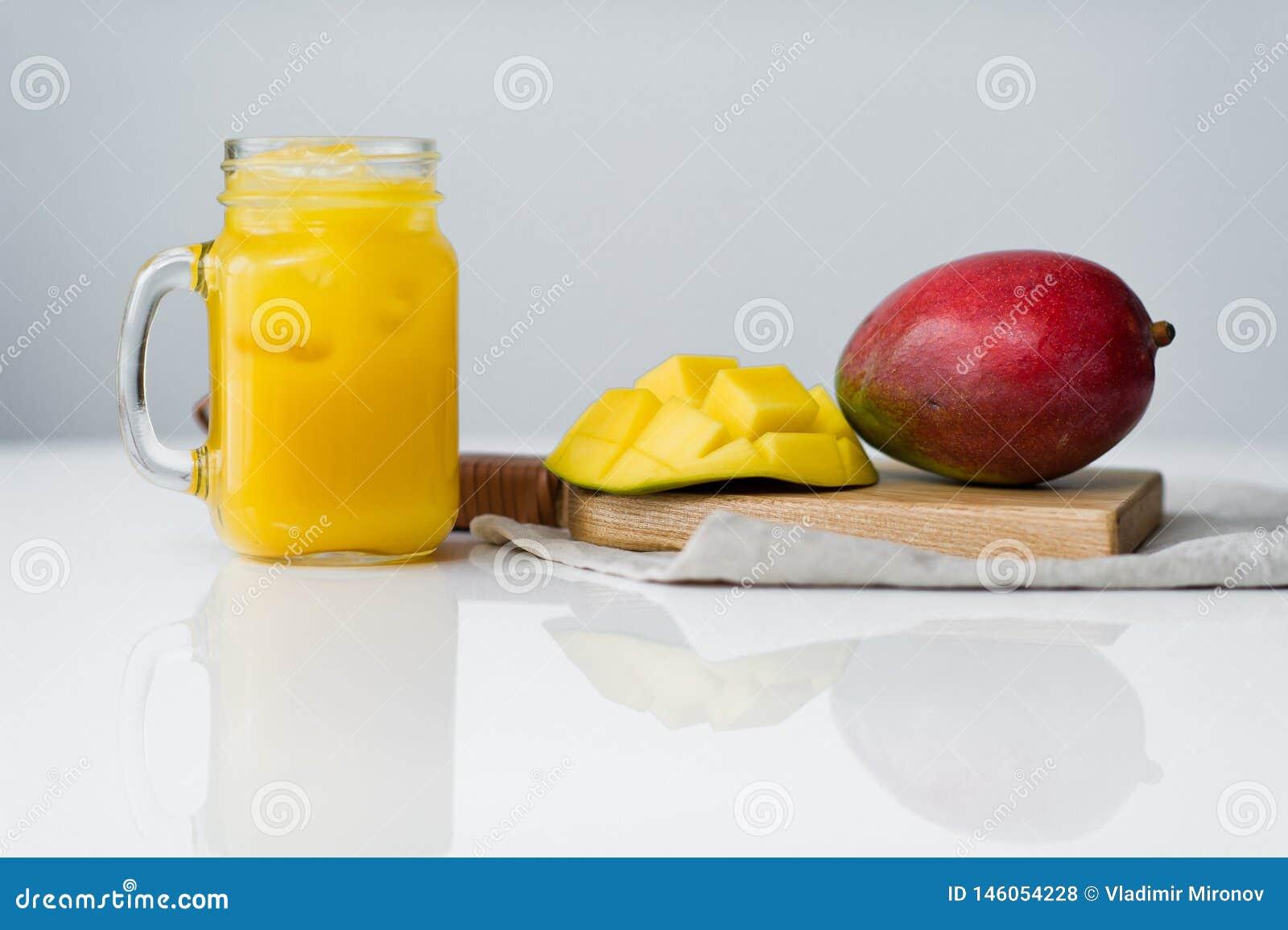Mango maduro y un vidrio de jugo del mango en una tajadera de madera