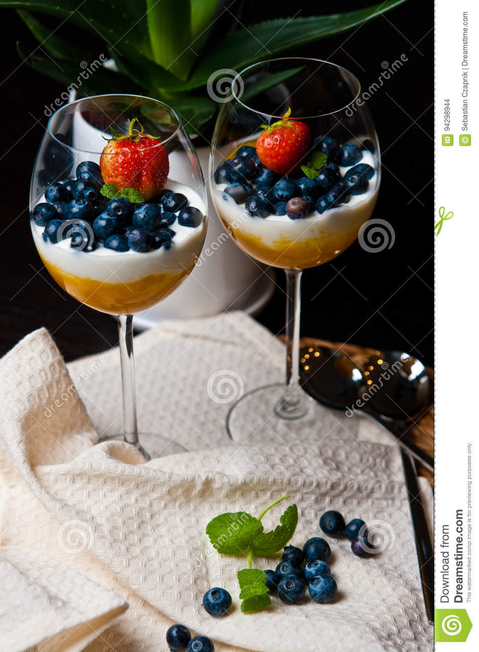 Mango mousse with blueberries in wine glasses
