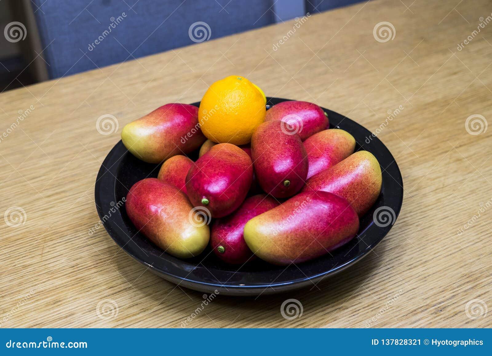 Mangos, naranjas, y limones de Apple en el cuenco en la cocina