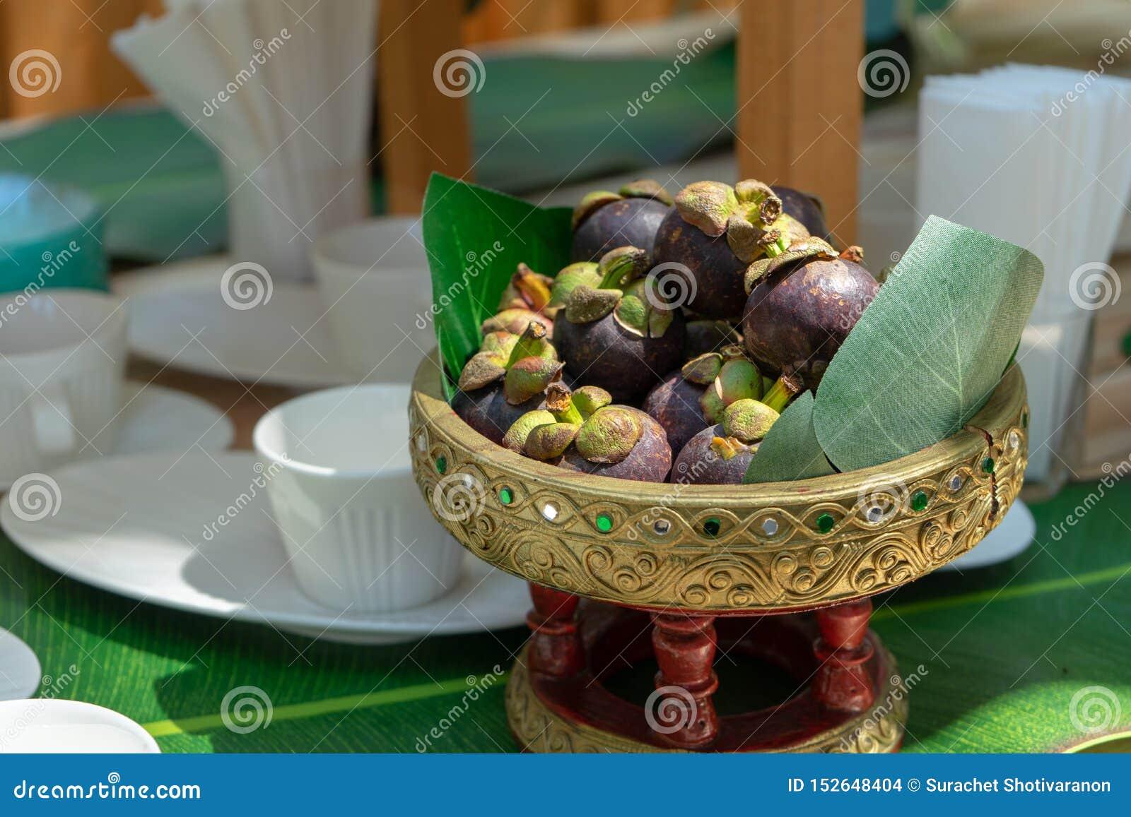 Mangostán en el vintage tailandés asiático phan o bandeja en la tabla de madera Ellos listos para servir por tiempo del descanso