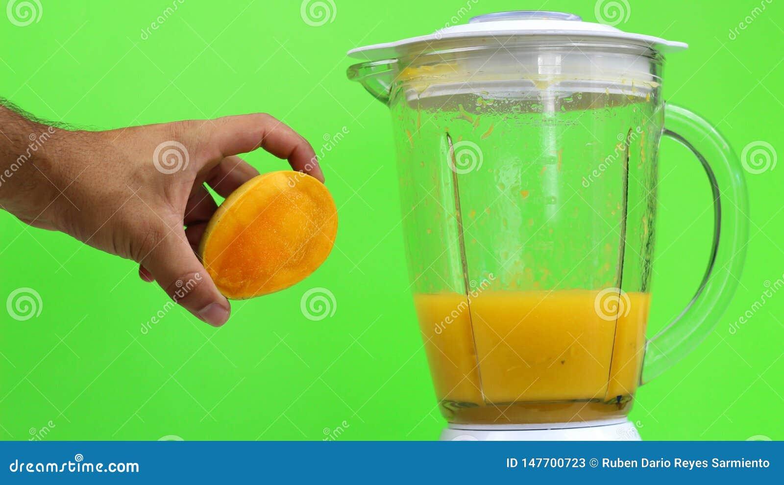 Mangowy sok z blender na zielonym tle,