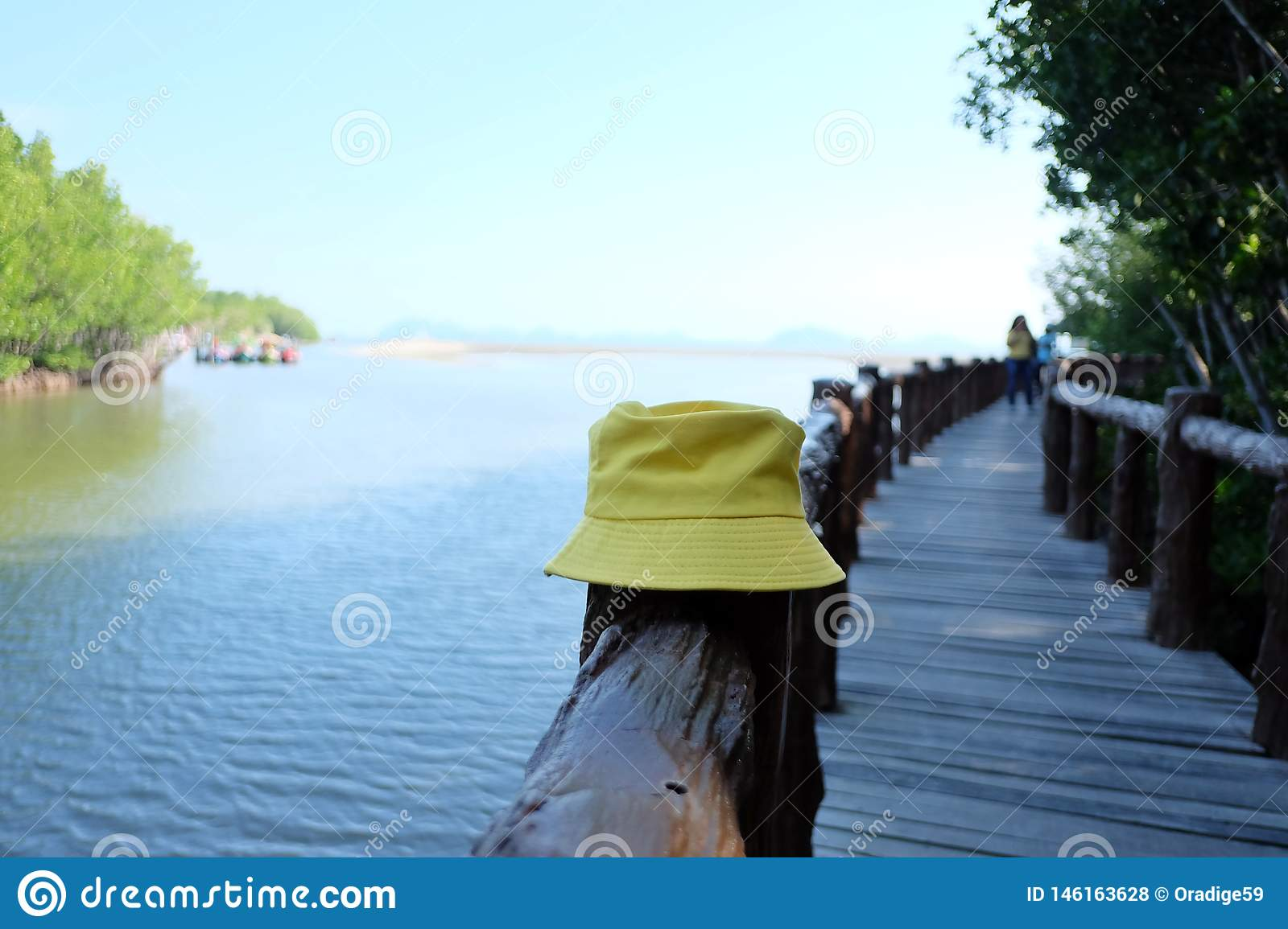 A yellow woman hat on a pole at th.e wooden bridge