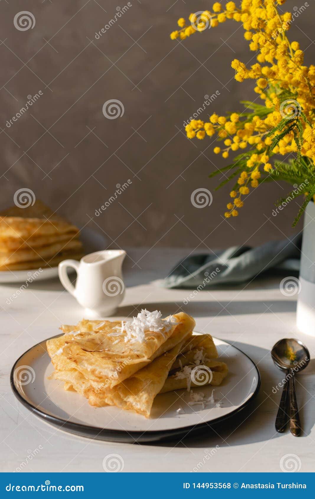 Manhã, café da manhã - panquecas tradicionais do blini do russo, crepes franceses chantiliy, flor da mimosa