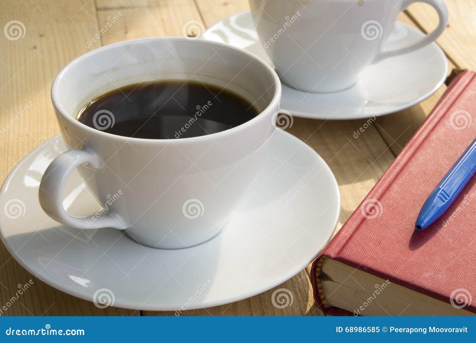 Manhã da xícara de café com a pena vermelha do azul do livro