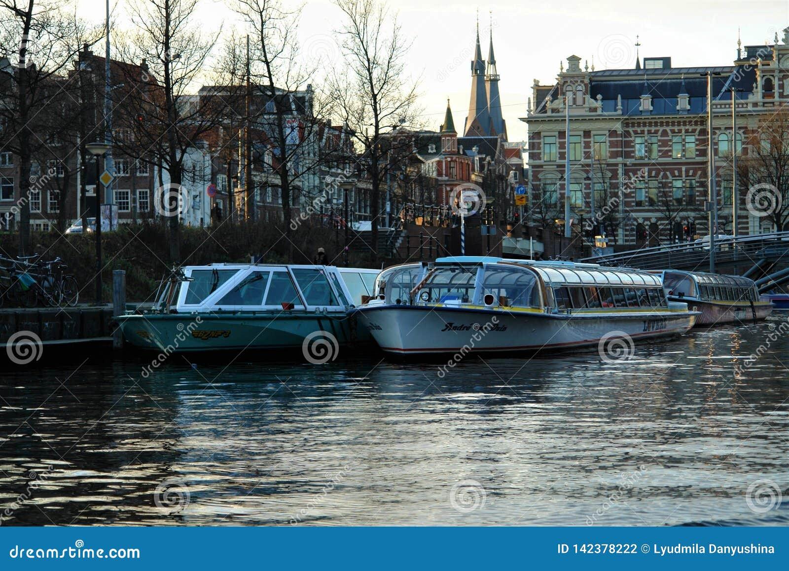 Manhã em Amsterdão Rua da água com os barcos no cais, refletido na água quieta