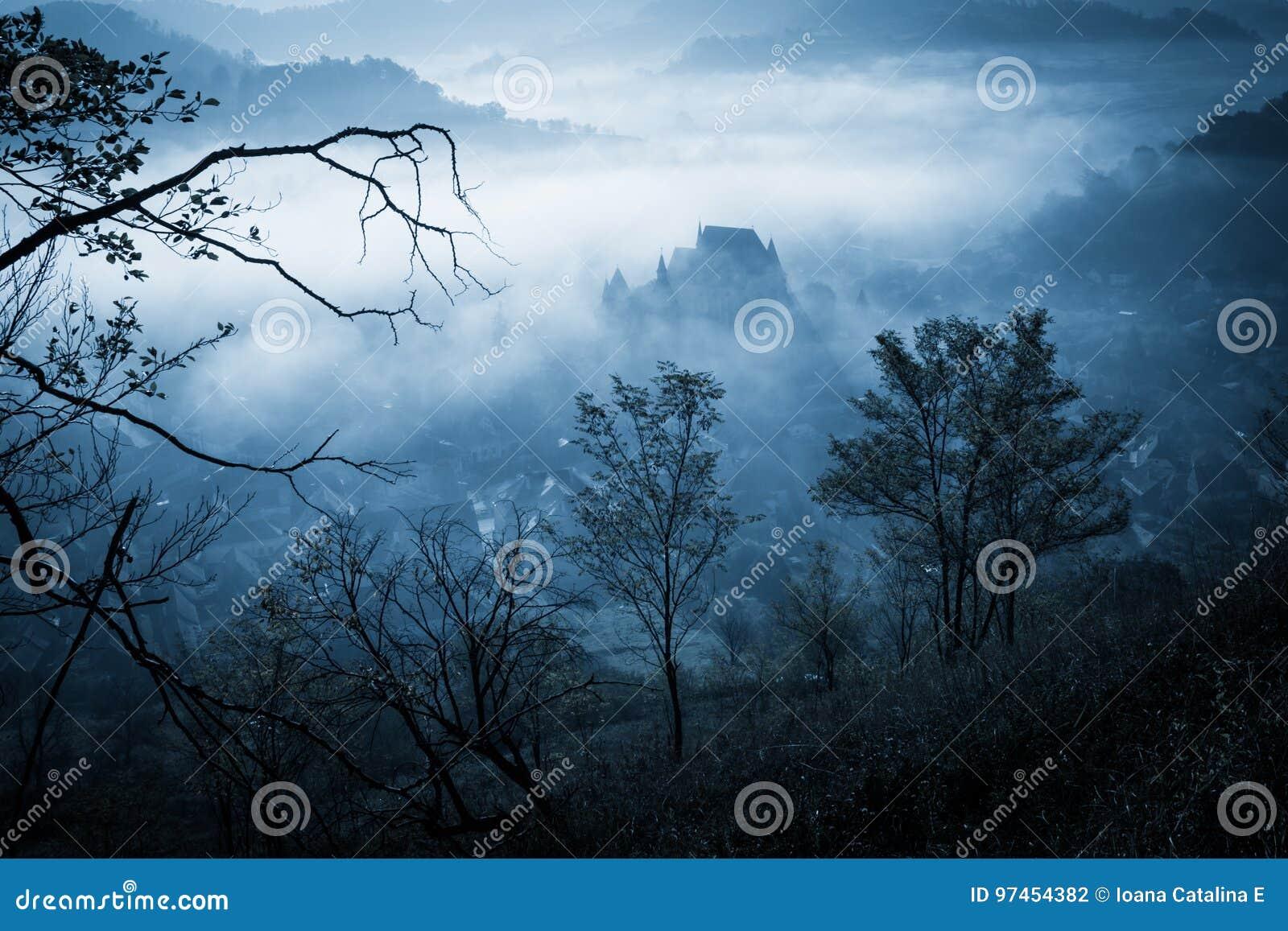 Manhã enevoada misteriosa sobre a vila de Biertan, a Transilvânia, Romênia