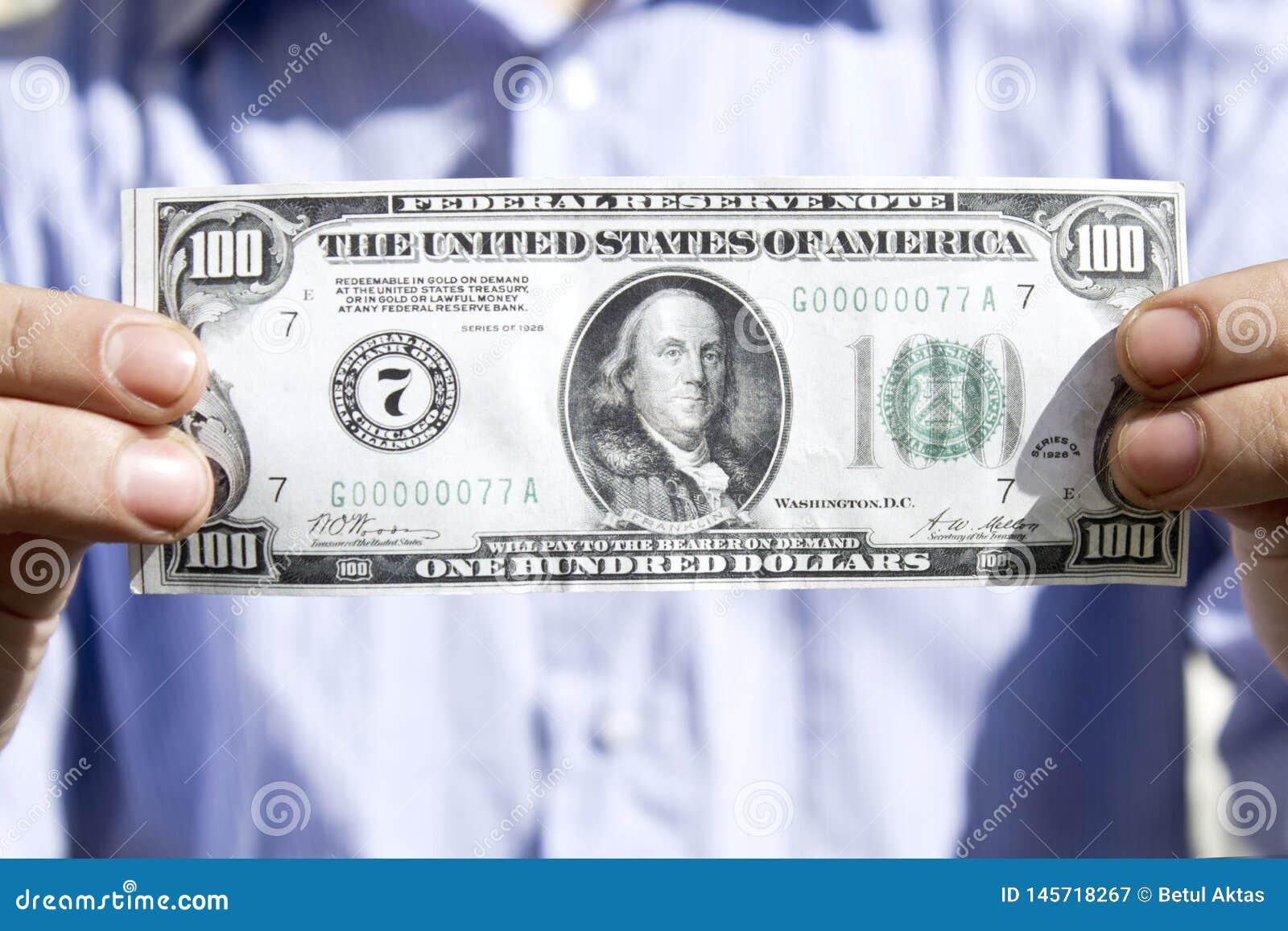 Manhänder som rymmer en U S dollar hundra