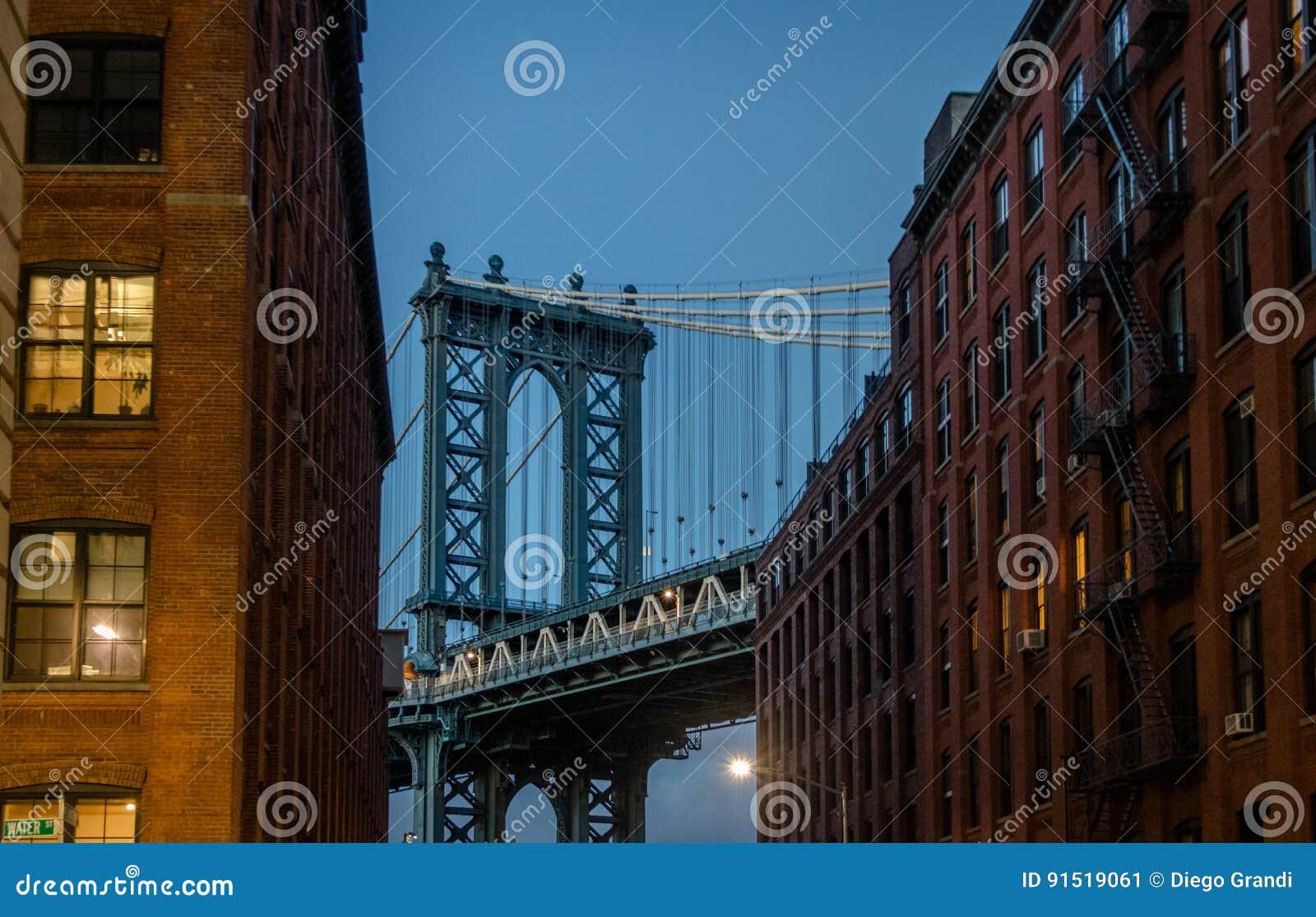 Manhattan Bridge seen from Dumbo between brick buildings on Brooklyn at sunset - New York, USA