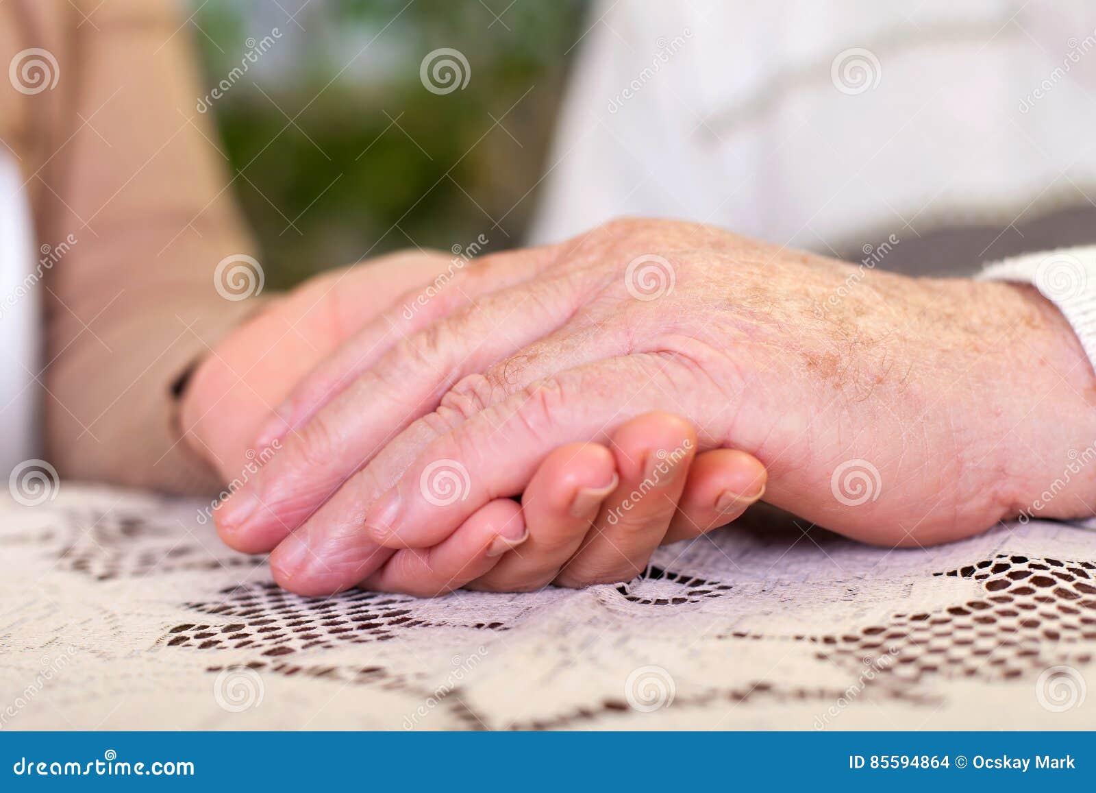 Mani anziane che tengono le mani del ` s di personale sanitario