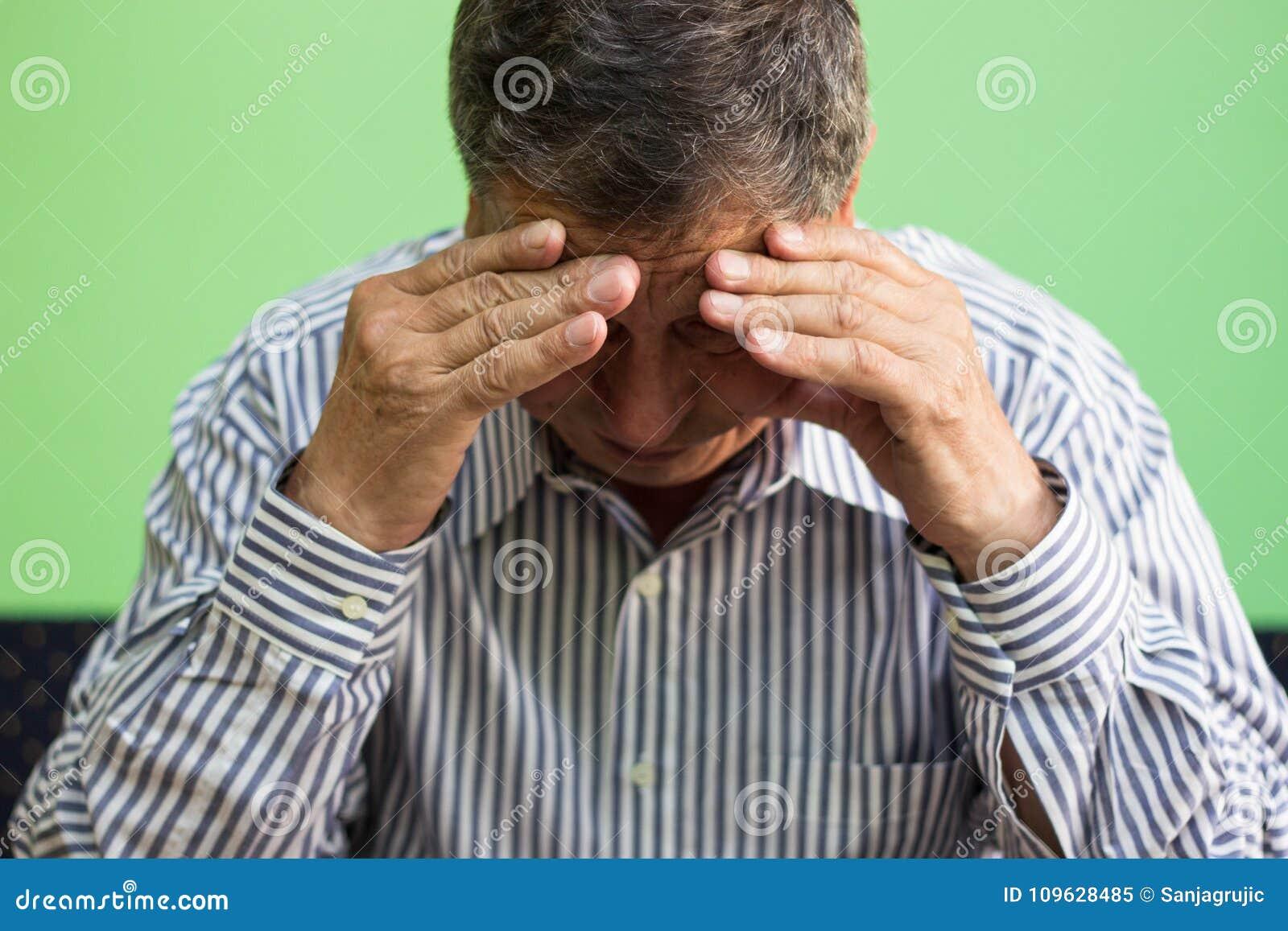 Mani che coprono fronte dell uomo senior