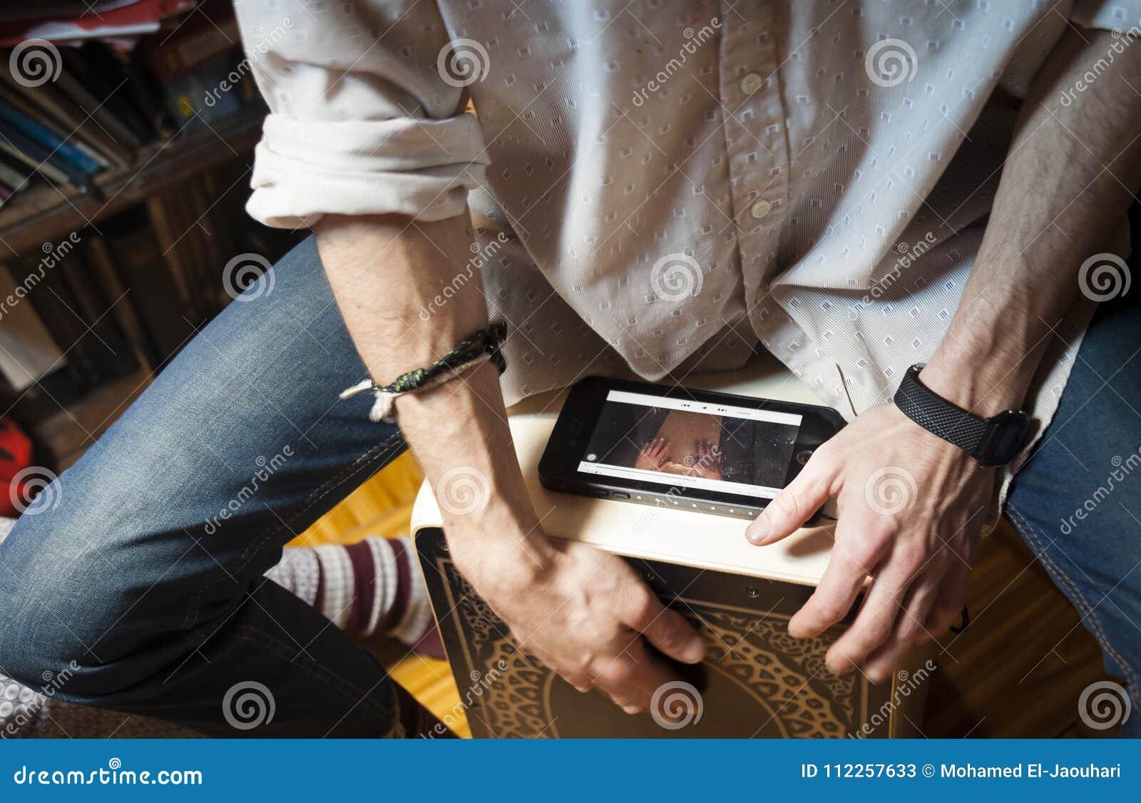 Mani che giocano percussione con una scatola di flamenco e uno smartphone