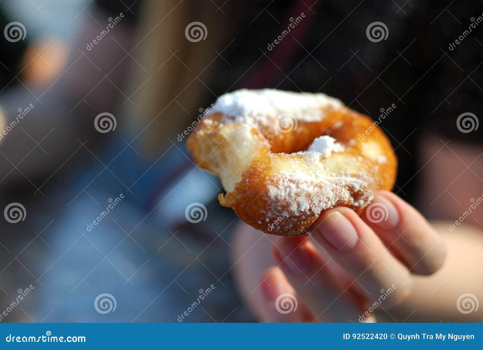 Mani che giudicano ciambella bited spolverata con la fine in polvere dello zucchero su