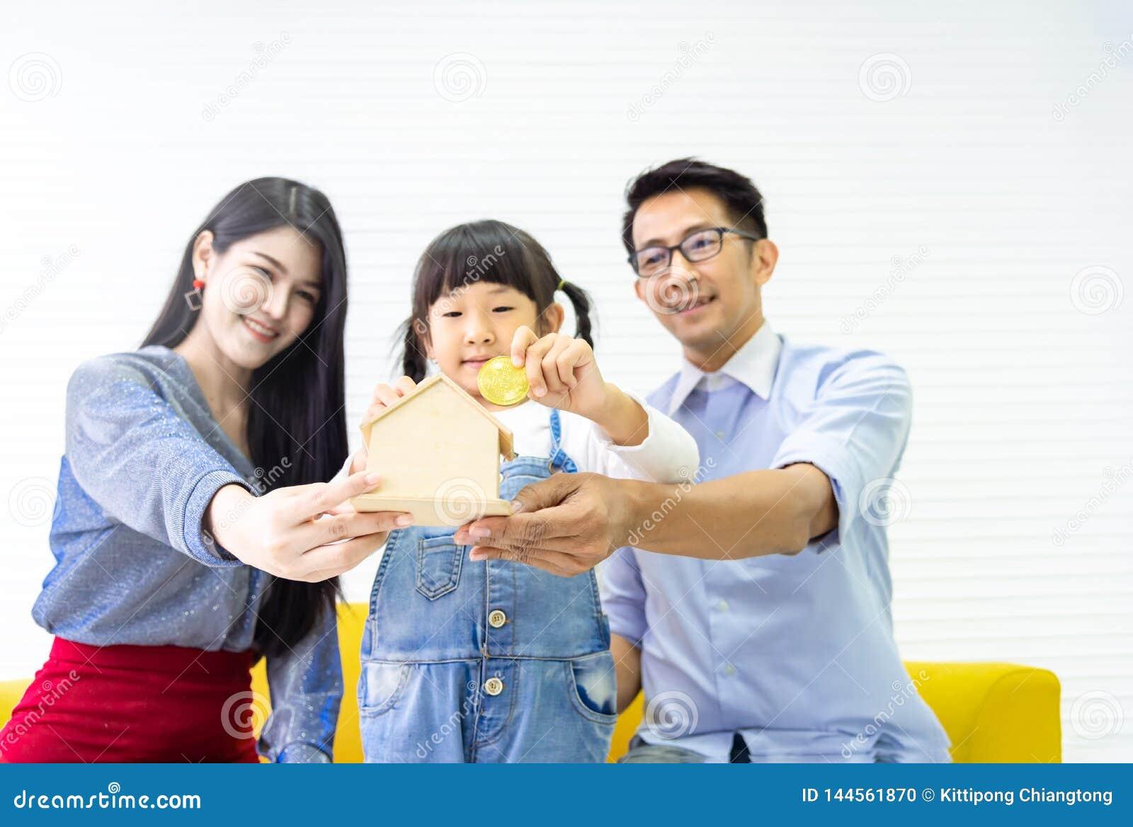 Mani che tengono banca piggy Soldi di risparmio della famiglia alla banca domestica di legno Bambina graziosa e famiglia che mett