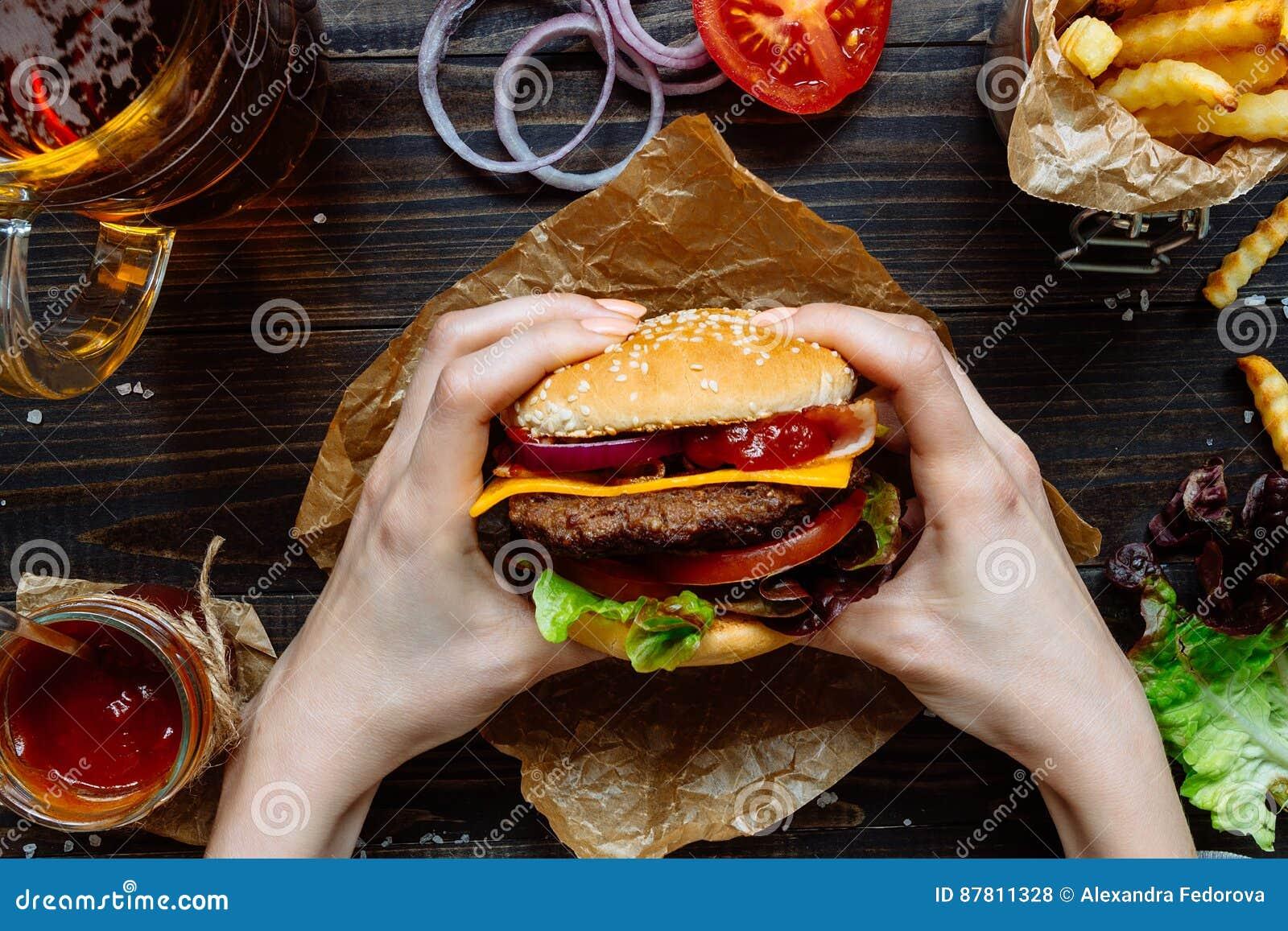 Mani che tengono gli hamburger deliziosi freschi con le patate fritte, la salsa e la birra sulla vista di legno del piano d appog