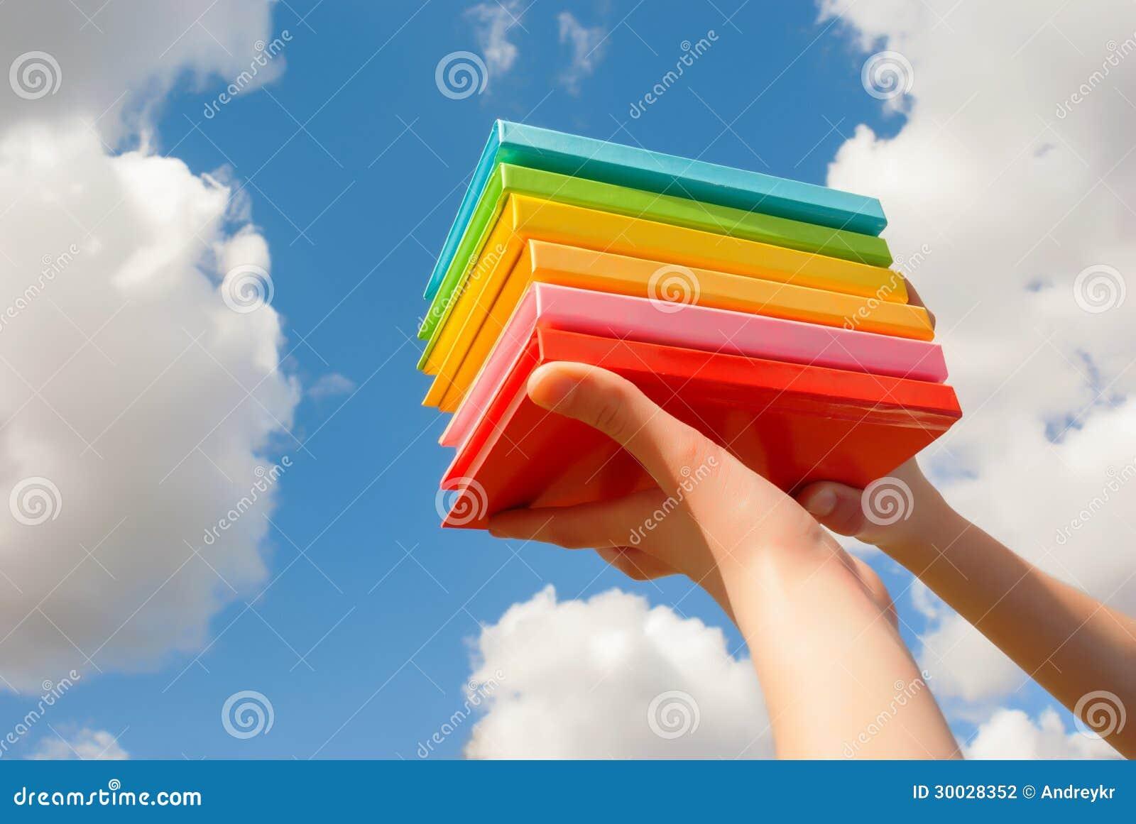 Mani che tengono i libri variopinti della copertina rigida