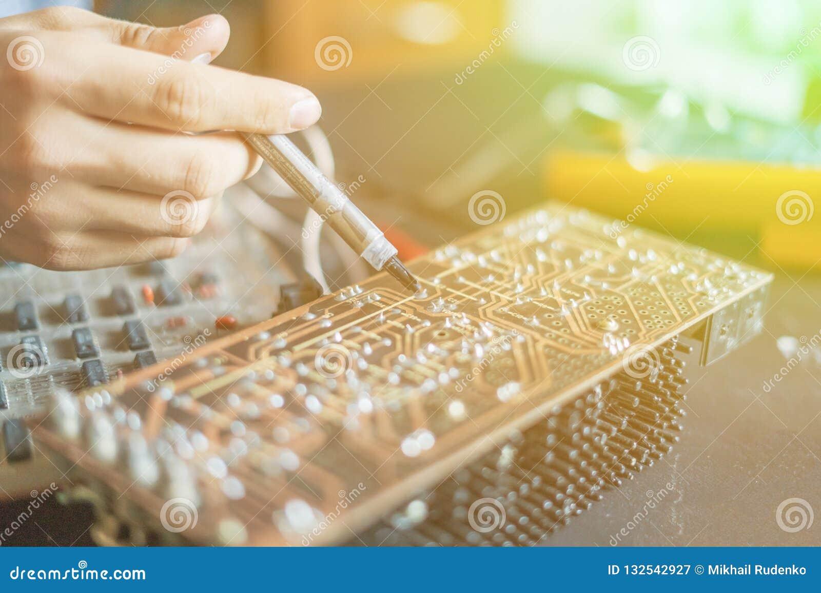 Mani che tengono il chip f del bordo del computer di riparazione e della siringa