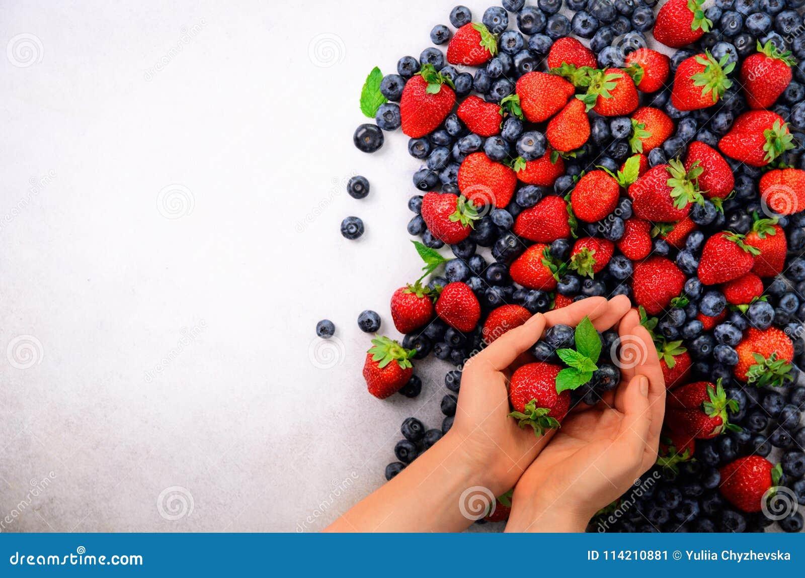 Mani che tengono le bacche fresche Cibo pulito sano, essendo a dieta, alimento vegetariano, concetto della disintossicazione Chiu