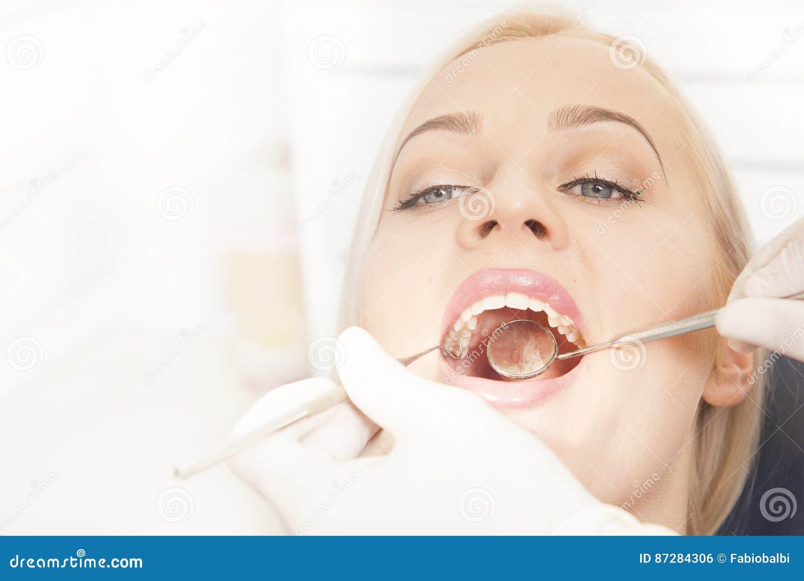 Mani del dentista che funzionano con i denti femminili