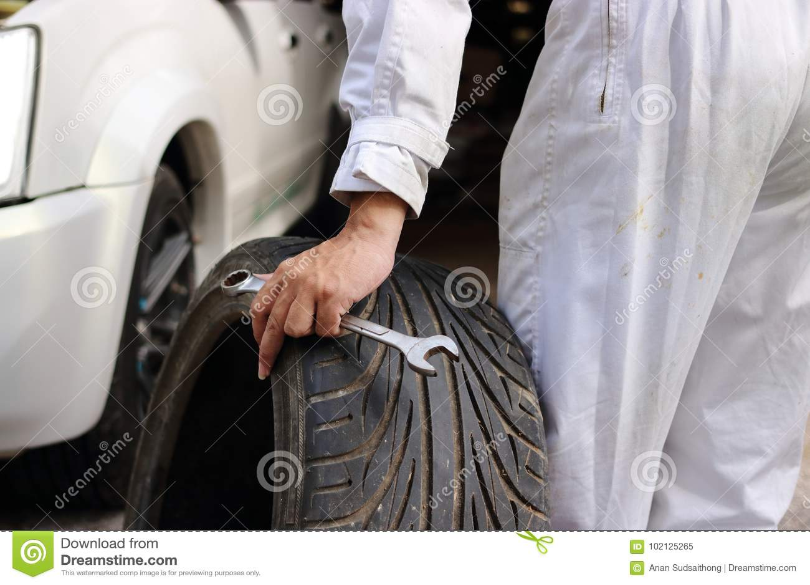Mani del meccanico automobilistico in uniforme con la gomma e la chiave per l automobile di riparazione ai precedenti del garage