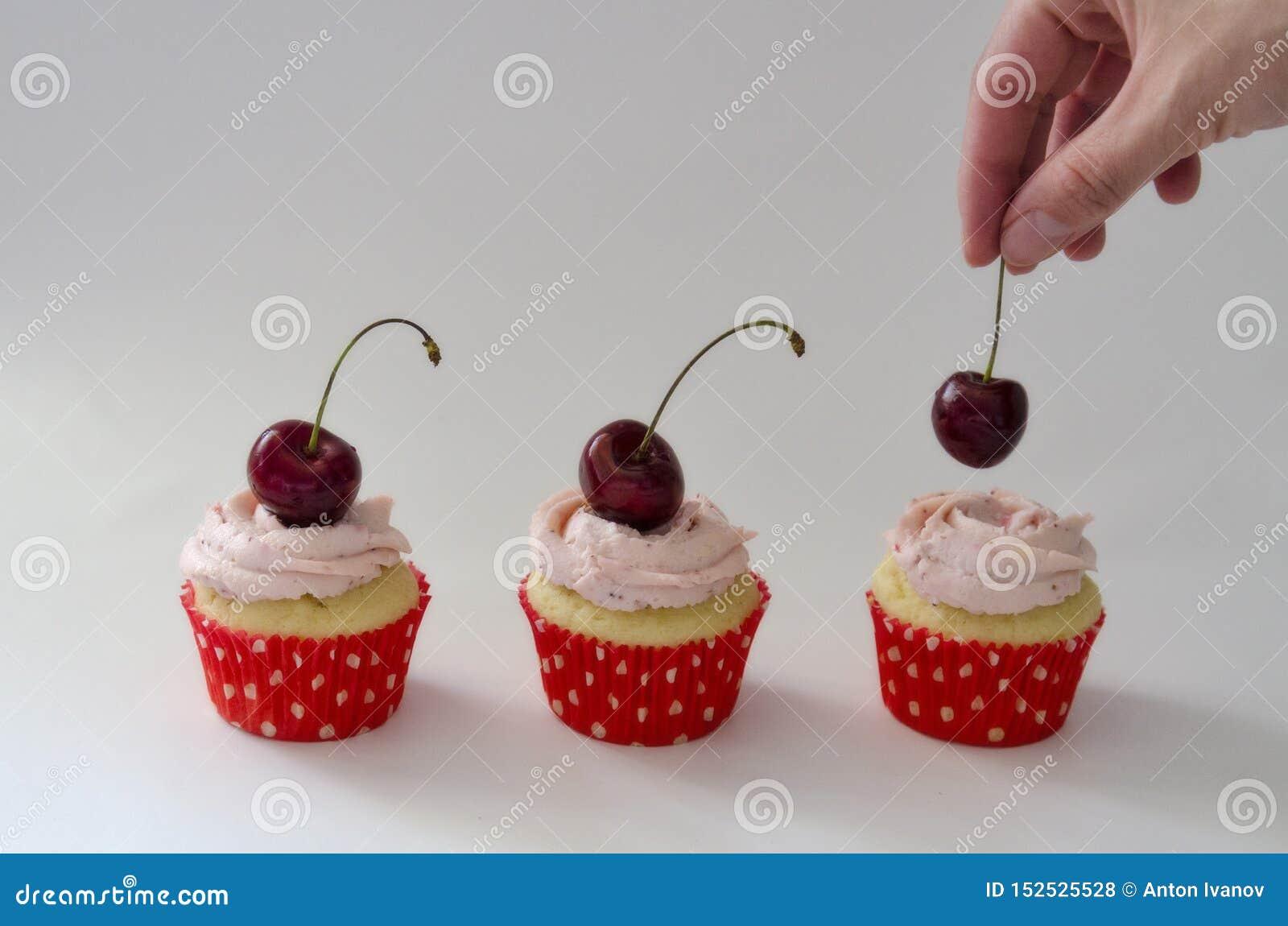 Mani del primo piano del cuoco unico che decorano i bign? con le bacche colorate