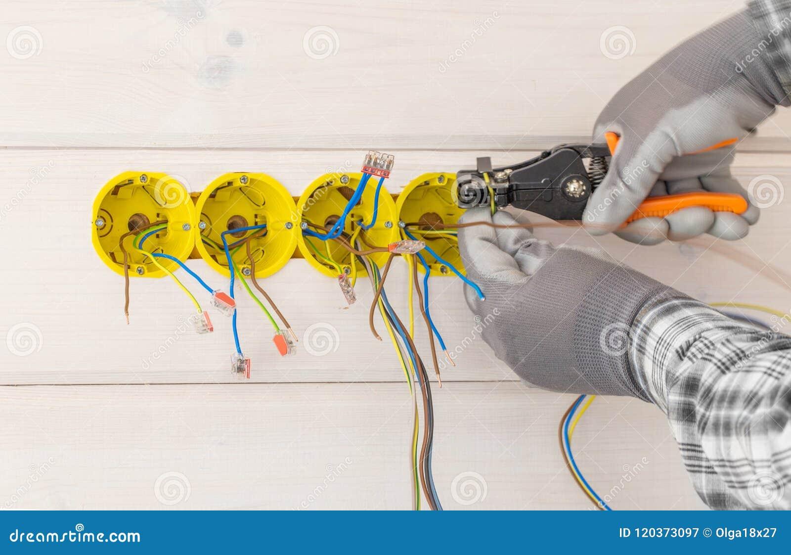 Mani dell elettricista che installano incavo elettrico con il cacciavite nella parete