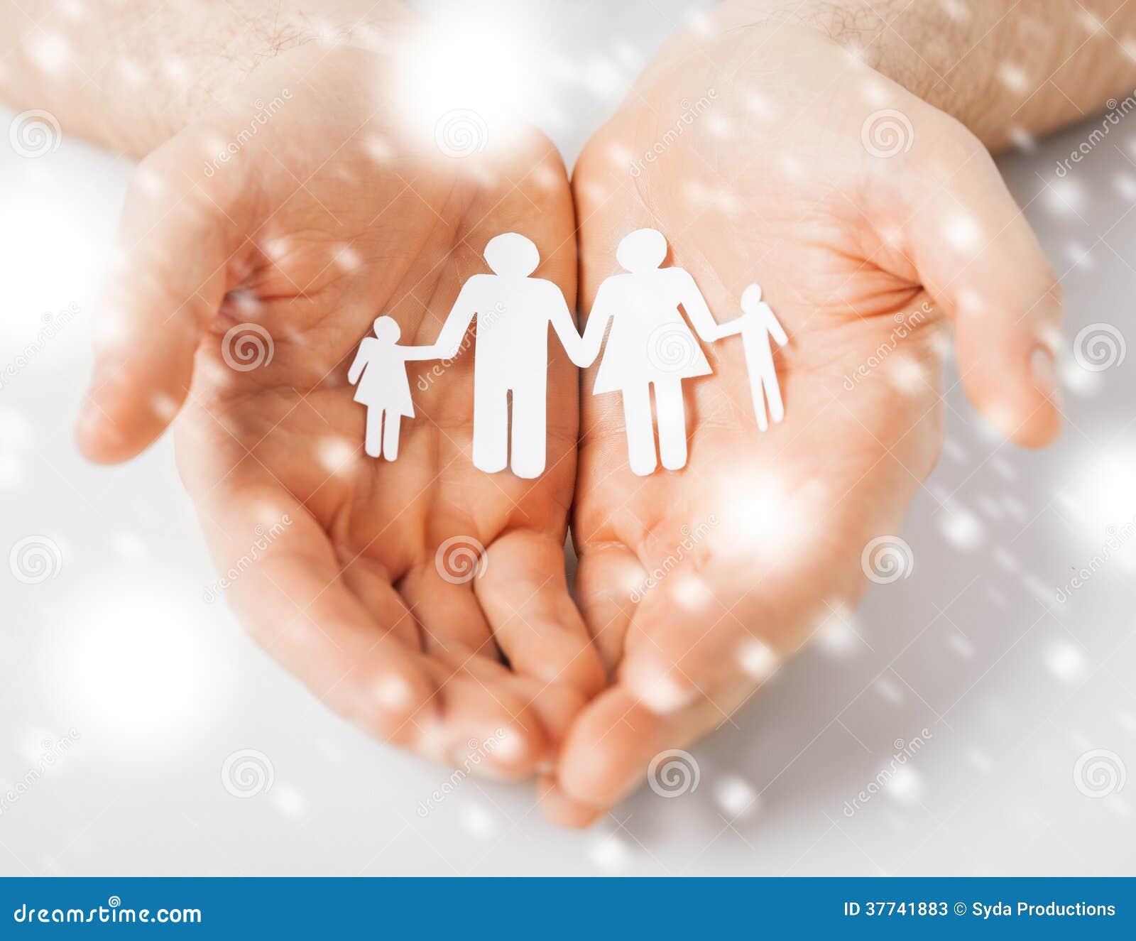 Mani dell uomo che mostrano famiglia della gente di carta