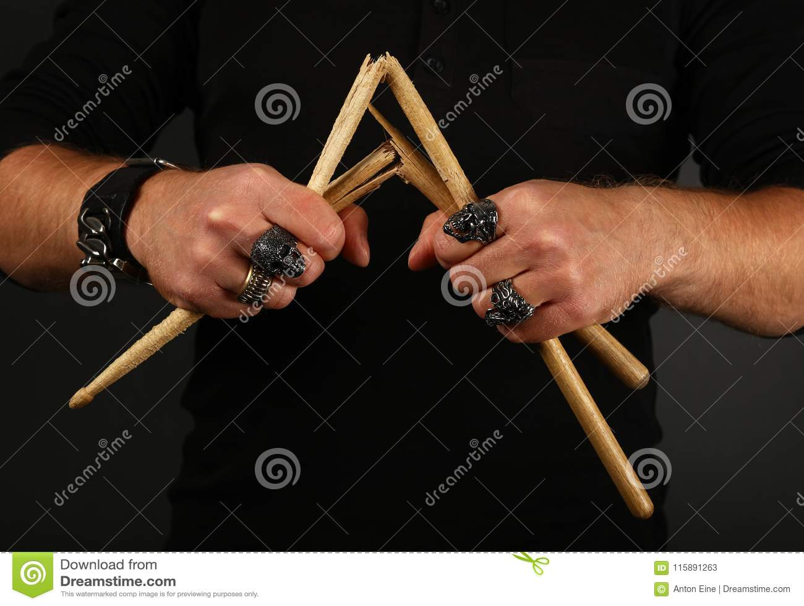 Mani dell uomo con le bacchette rotte sopra il nero