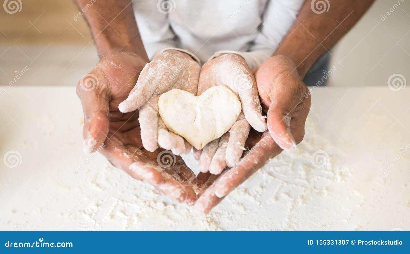 Mani dell uomo di afro che tengono le mani del bambino con la pasticceria a forma di del cuore