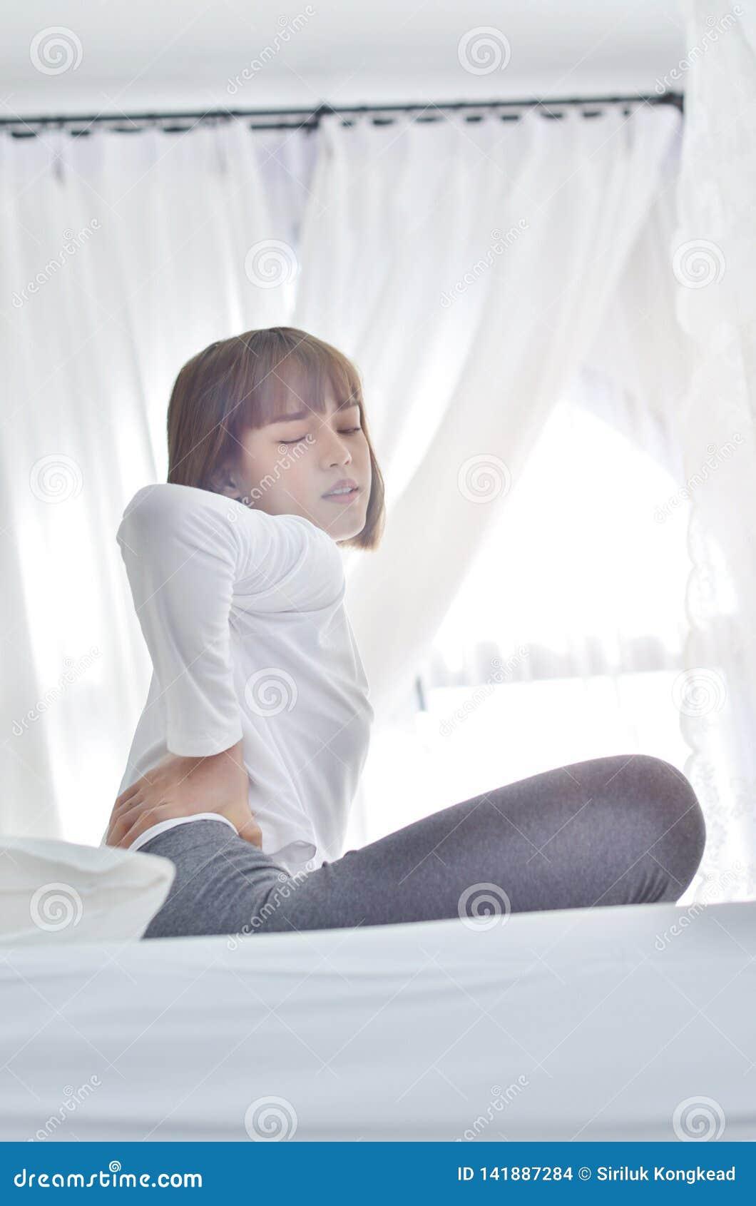 Mani della donna bianca sulla parte posteriore che ha dolore nella parte posteriore