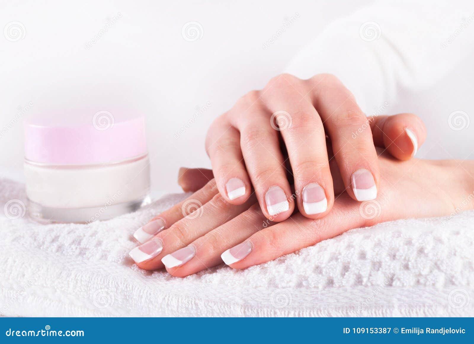 Mani della donna con il manicure francese e la crema per le mani rosa sull asciugamano bianco