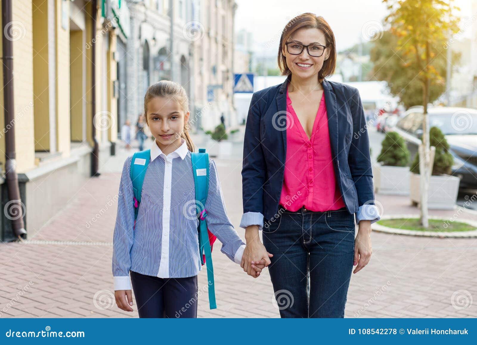 Mani della holding della figlia e della mamma Il genitore prende il bambino alla scuola