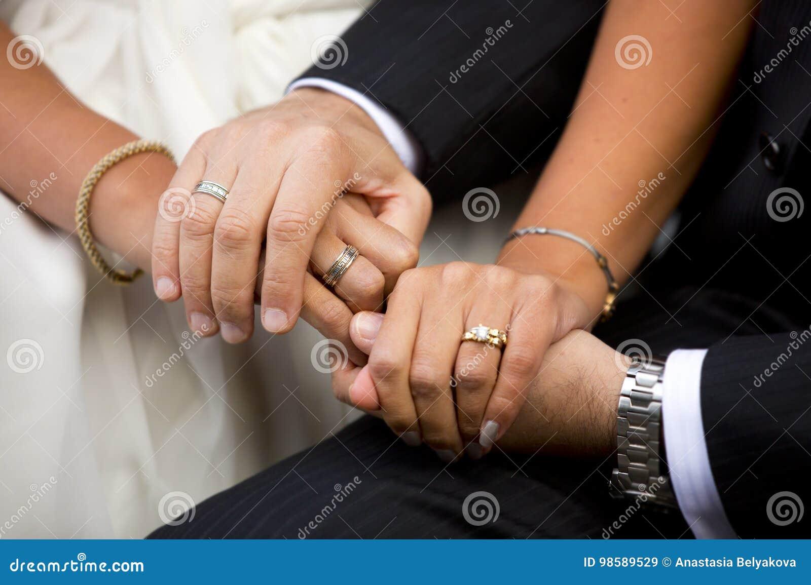 Mani della sposa e sposo, uomo e donna con le fedi nuziali