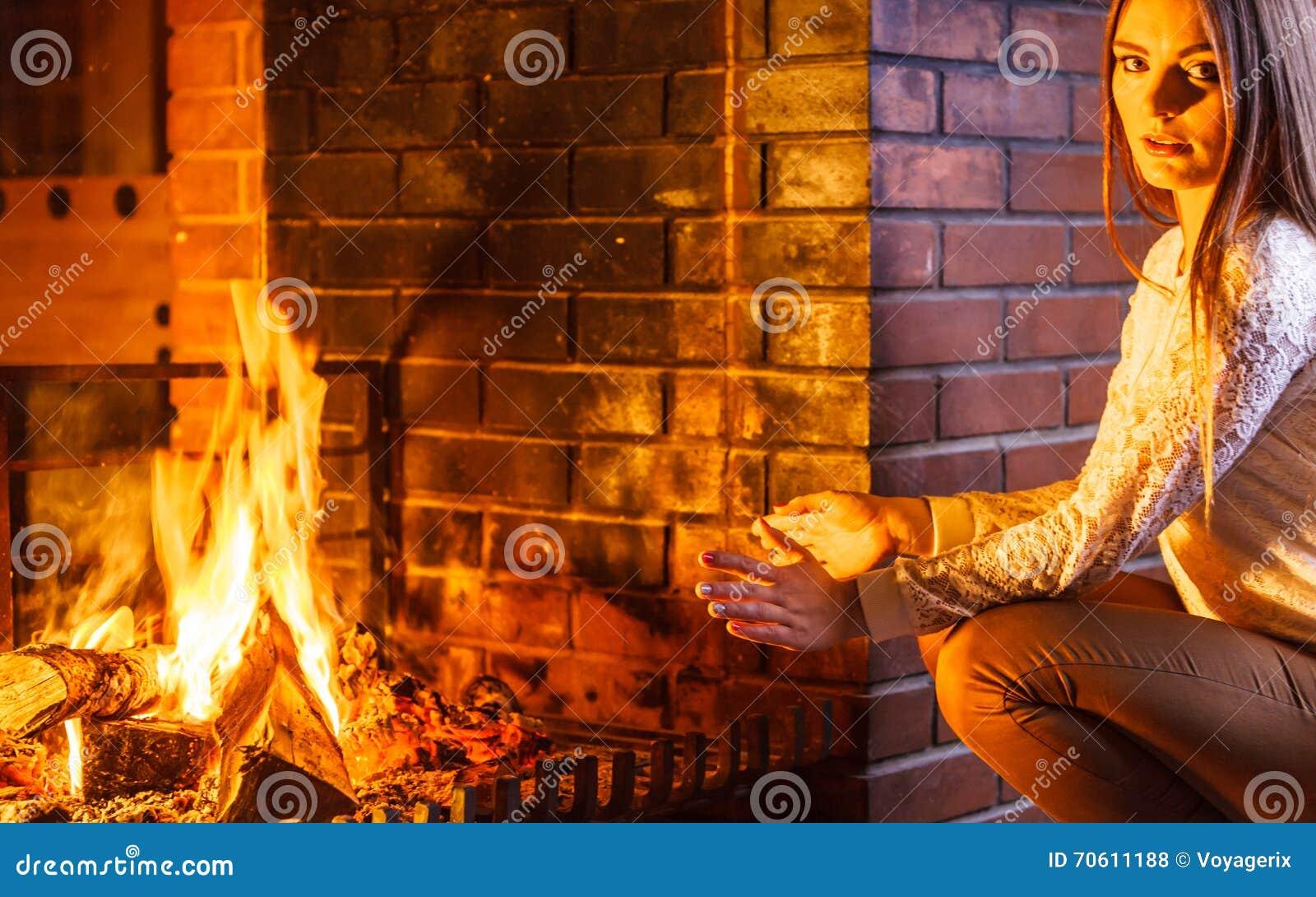 Mani di riscaldamento della donna su al camino casa di inverno