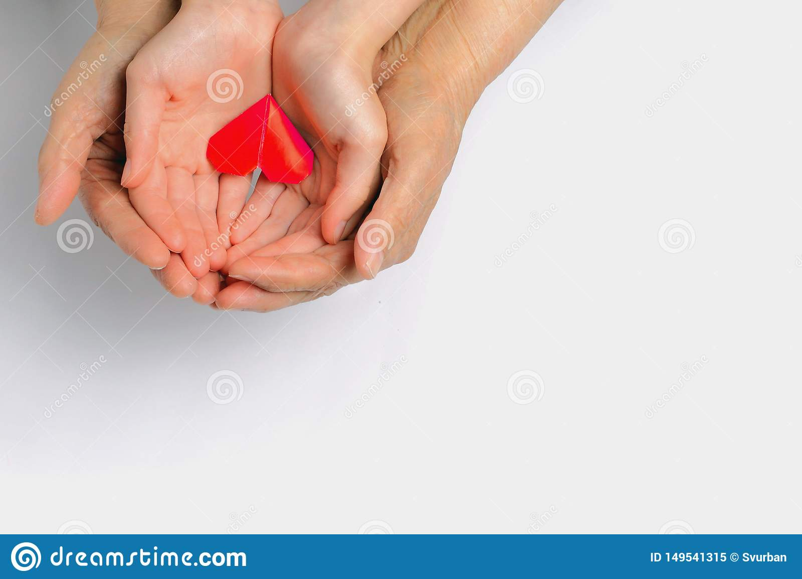 Mani di un adulto e di un bambino tenere un cuore rosso