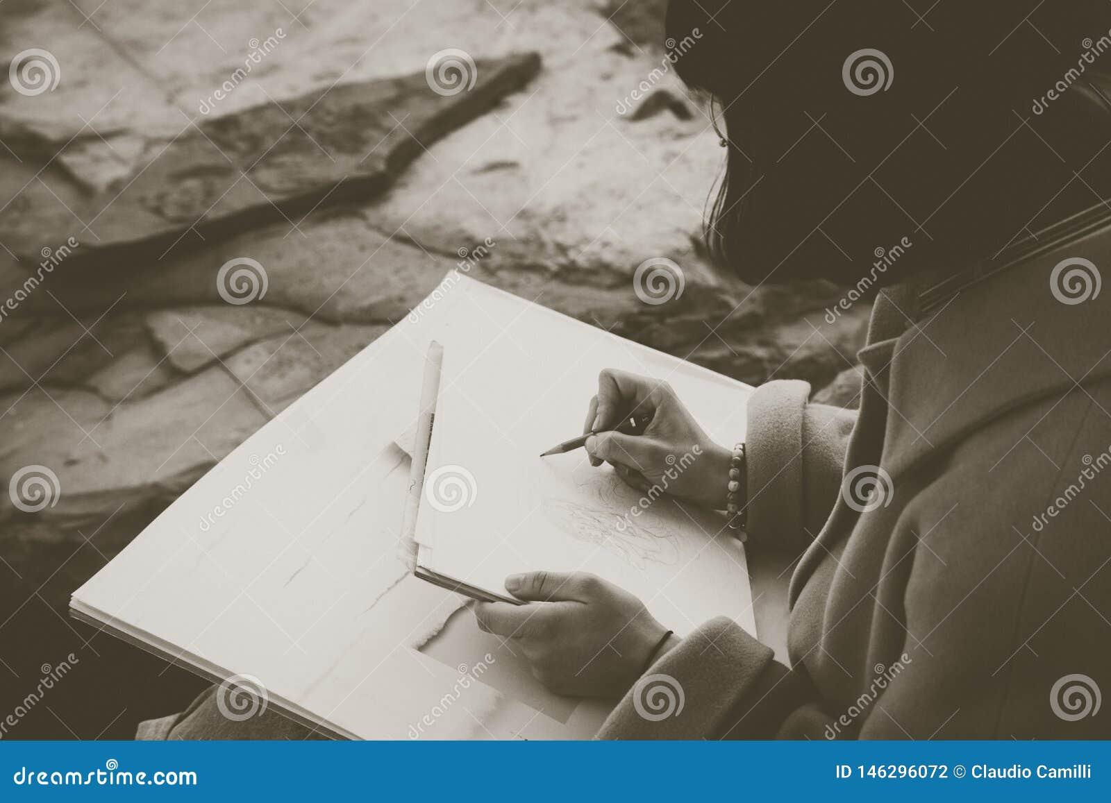 Mani di un disegno della ragazza con la matita
