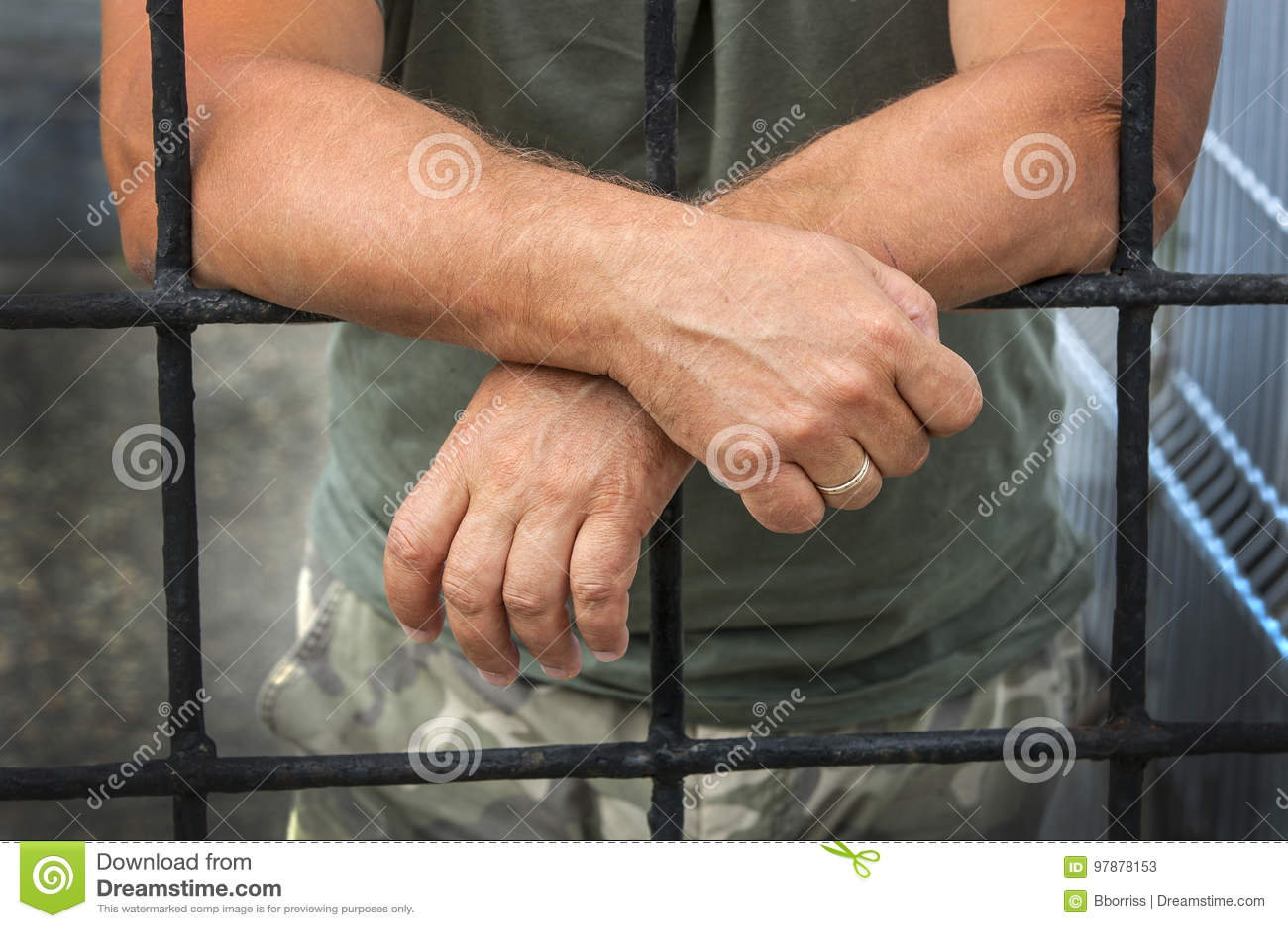 Mani di un uomo dietro le prigioni delle barre
