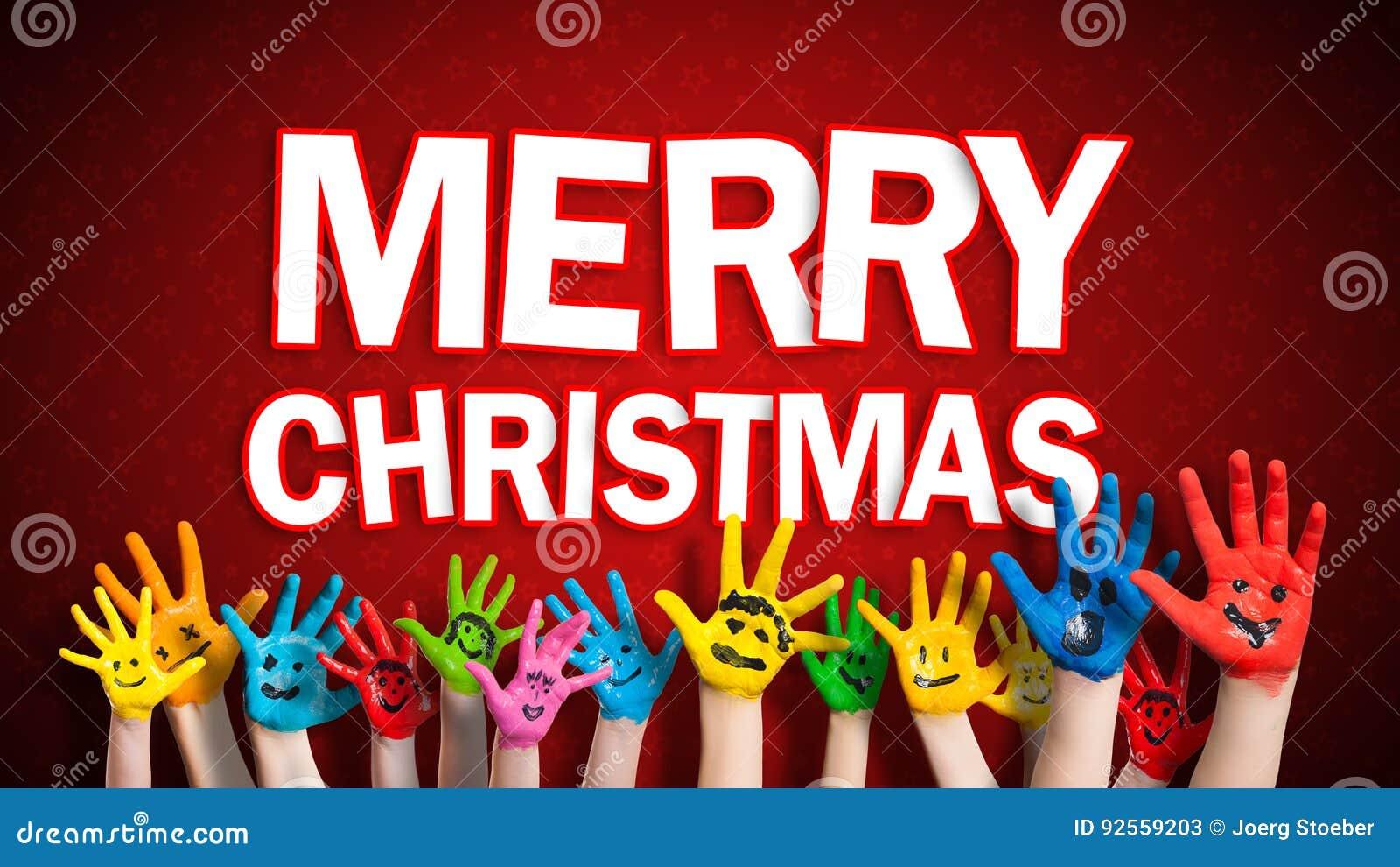 Mani dipinte dei bambini con lo smiley con il messaggio di Buon Natale