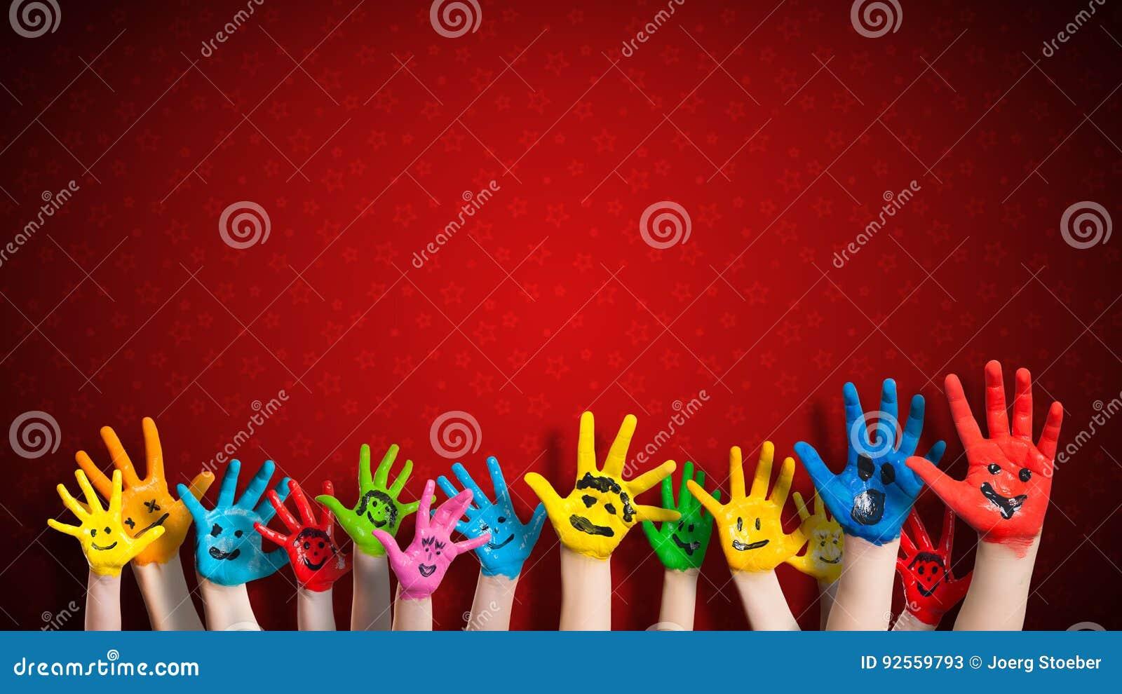 Mani dipinte dei bambini con lo smiley davanti al fondo di natale