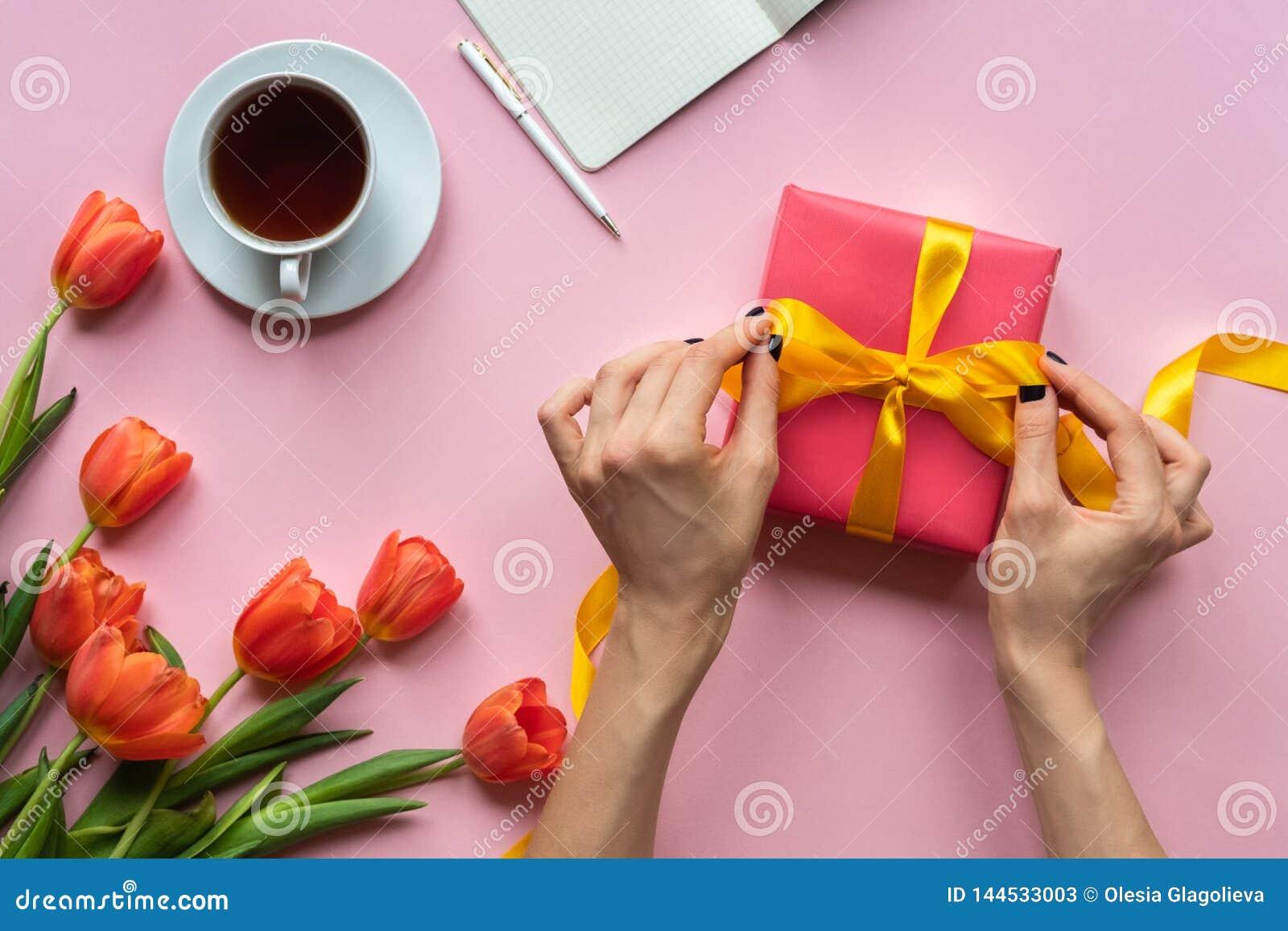 Mani femminili che tengono il contenitore di regalo rosso con il nastro giallo su fondo rosa