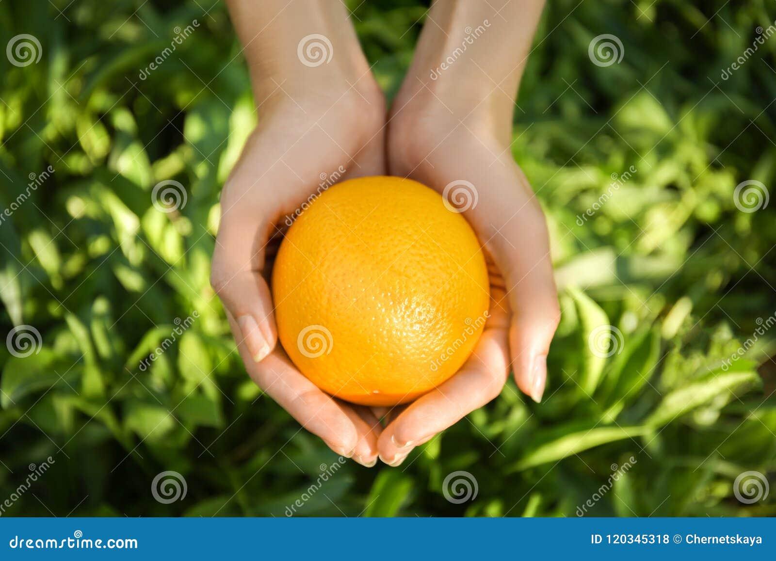 Mani femminili che tengono intera arancia su fondo verde